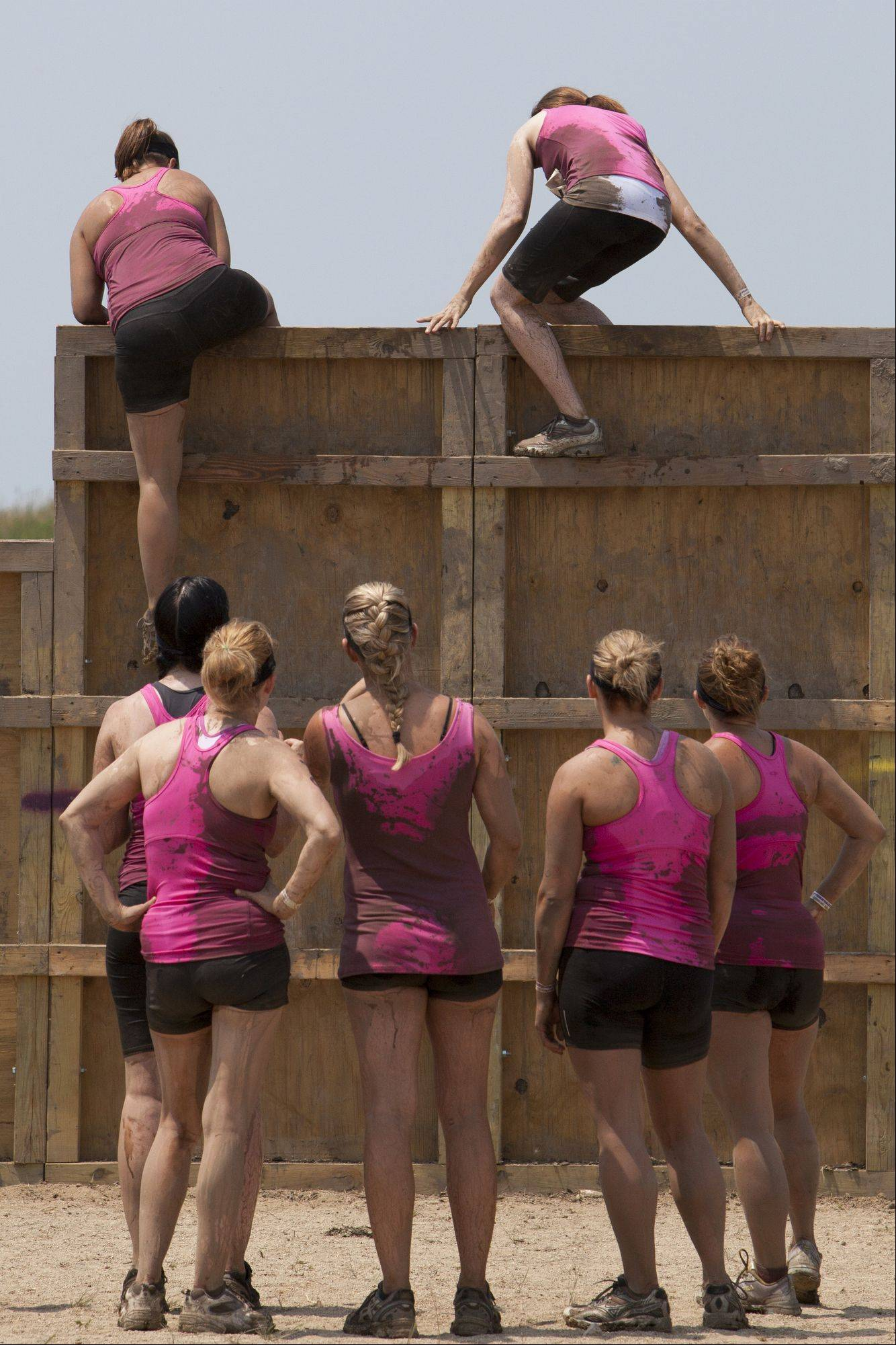 A team watches as the rest of their members climb over the first obstacle during the Dirty Girl Mud Run Saturday at the Lake County Fair Grounds.