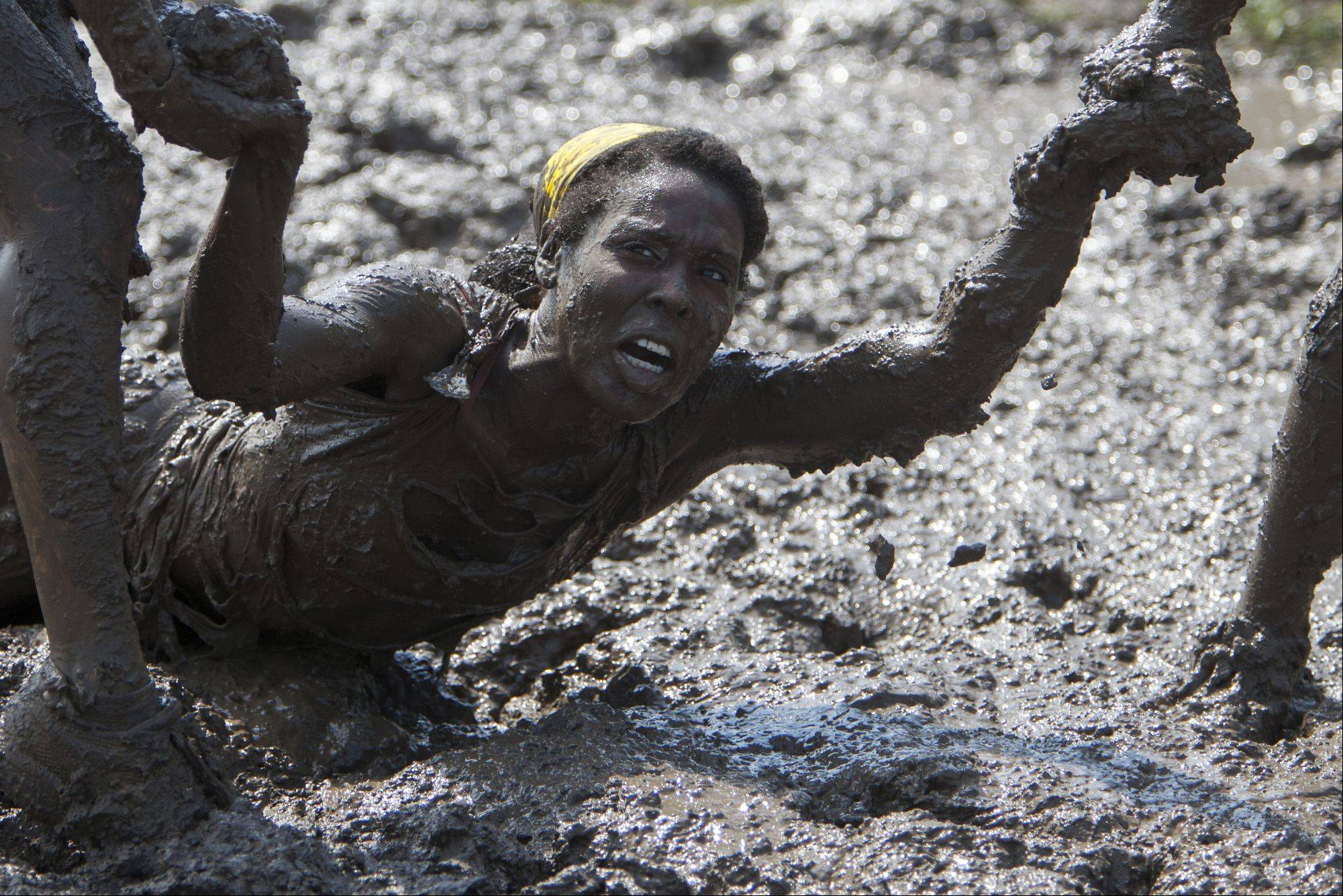 Joel Bissell/jbissell@dailyherald.comJoniqia Howard of Puerto Rico is helped out of the mud by two of her teammates during the Dirty Girl Mud Run on Saturday.