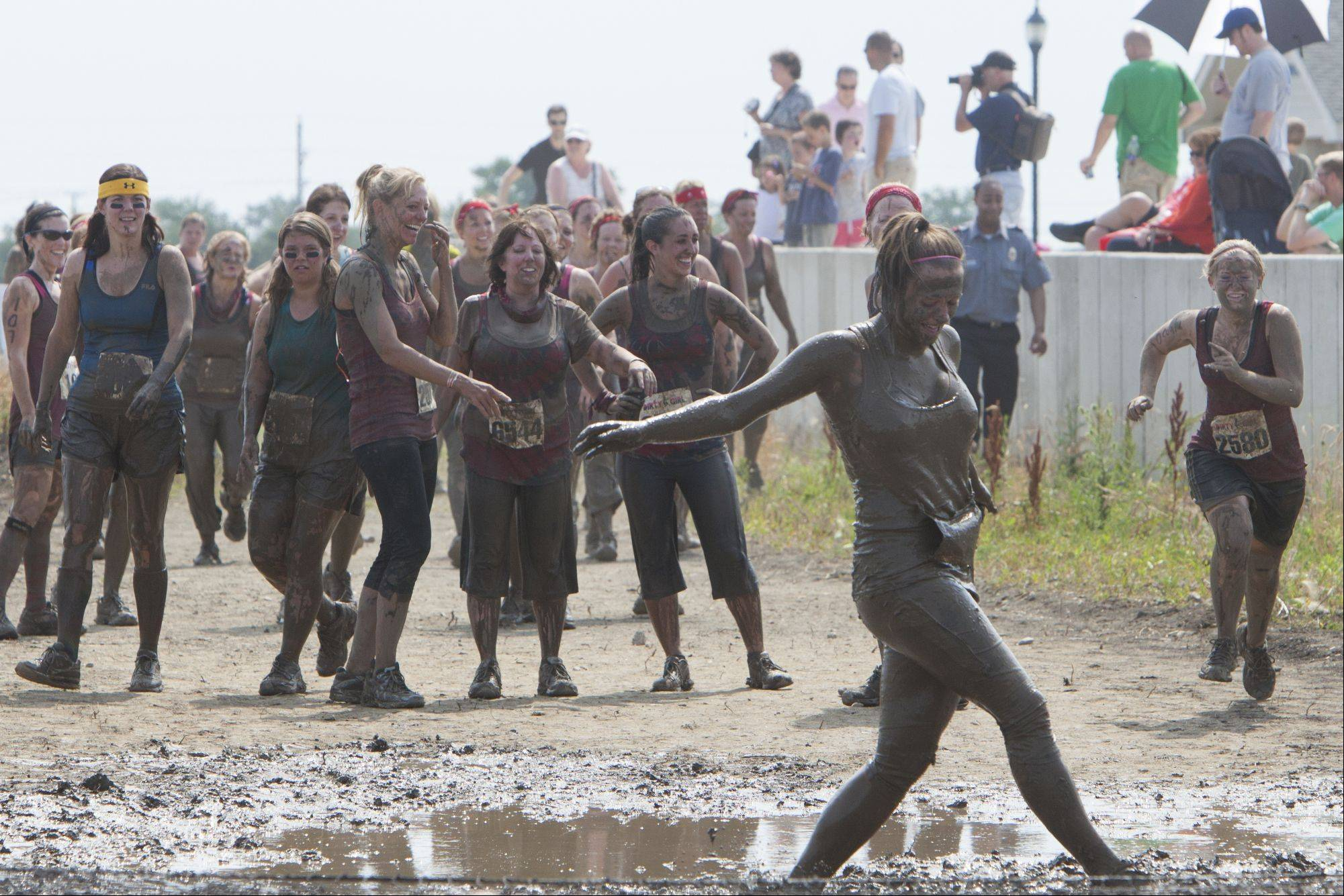 Jackie Newmann of Libertyville attempts to get up after diving into a mud pit as she is cheered on by her teammates during the Dirty Girl Mud Run.