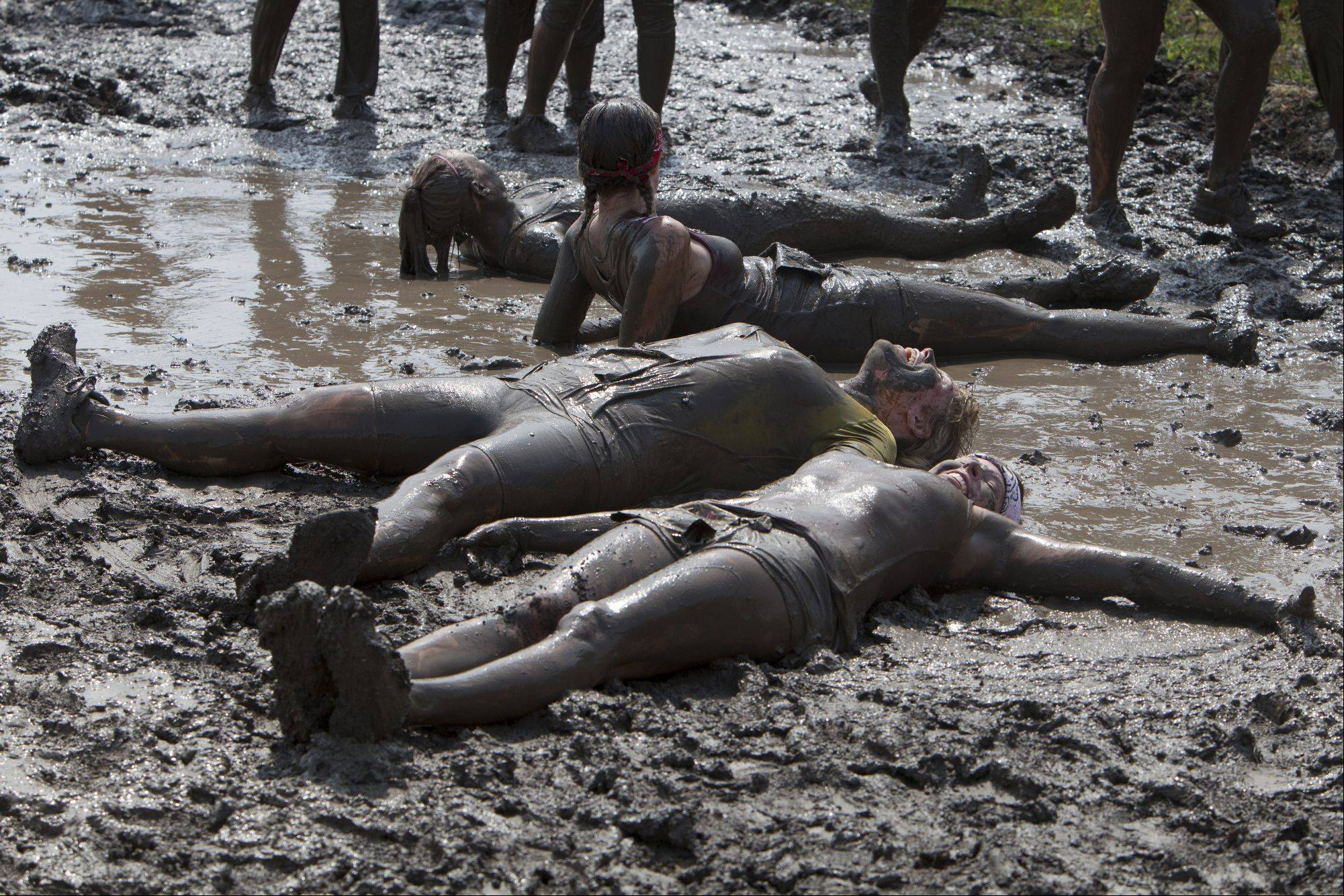 Robin Graham in yellow and Angie Bathel of Chicago make mud angels during the Dirty Girl Mud Run.