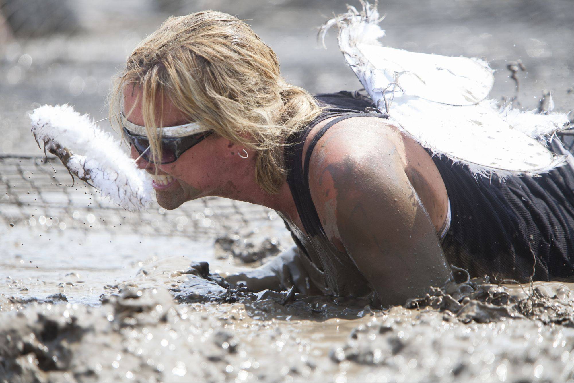 Anita Fuller of Antioch attempts pull herself out of the mud after army crawling through about 30 feet of mud during the Dirty Girl Mud Run Saturday at the Lake County Fair Grounds.