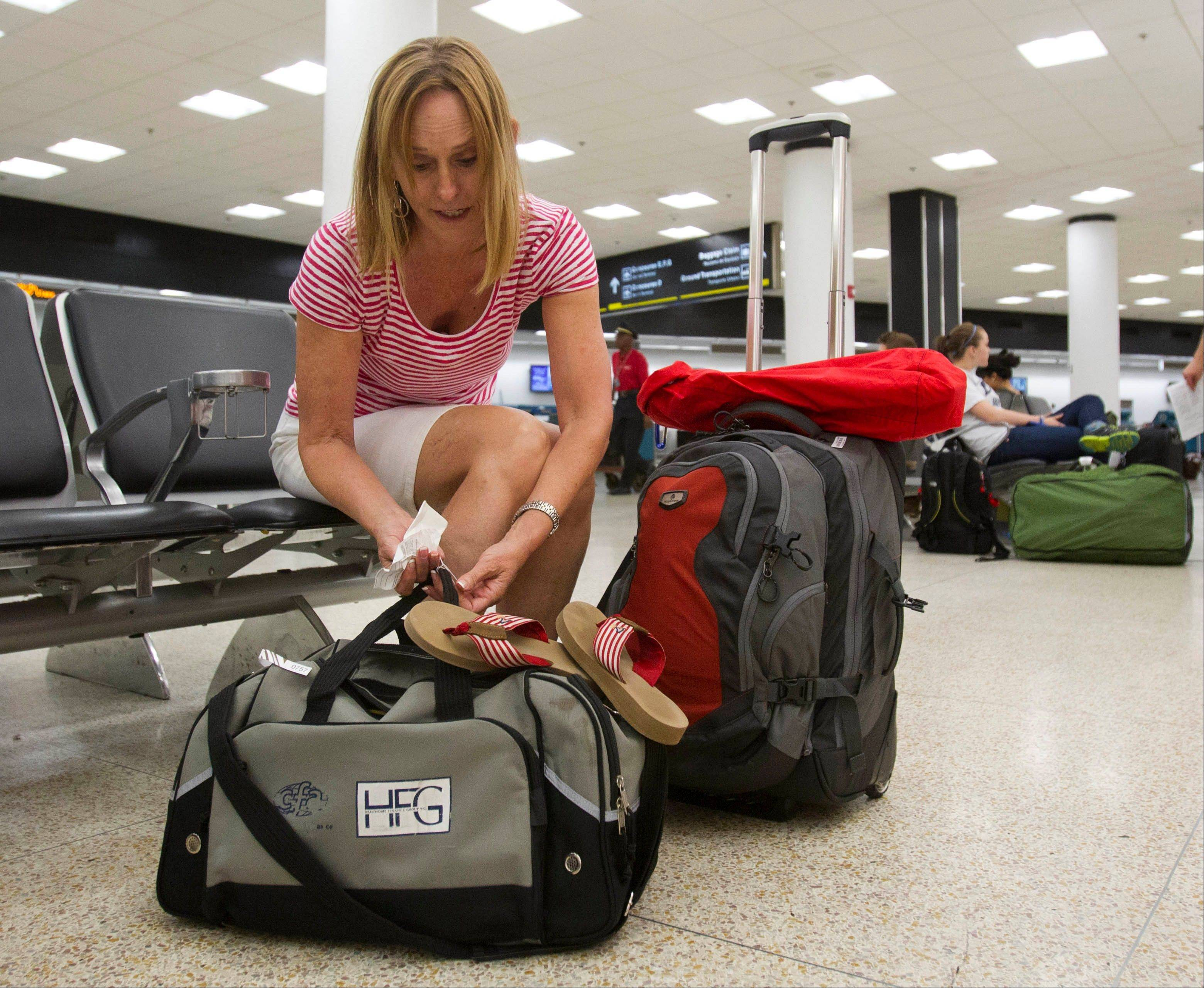 Pat Burns, of San Diego, prepares her luggage for check-in at Miami International Airport in Miami last Friday. Burns, after an overnight stay in Miami, is traveling to the Galapagos Islands in Ecuador for the Fourth of July holiday. For the first time in five years Independence Day falls on a Wednesday, leaving travelers unsure when to celebrate and worrying those who make a living off tourists.