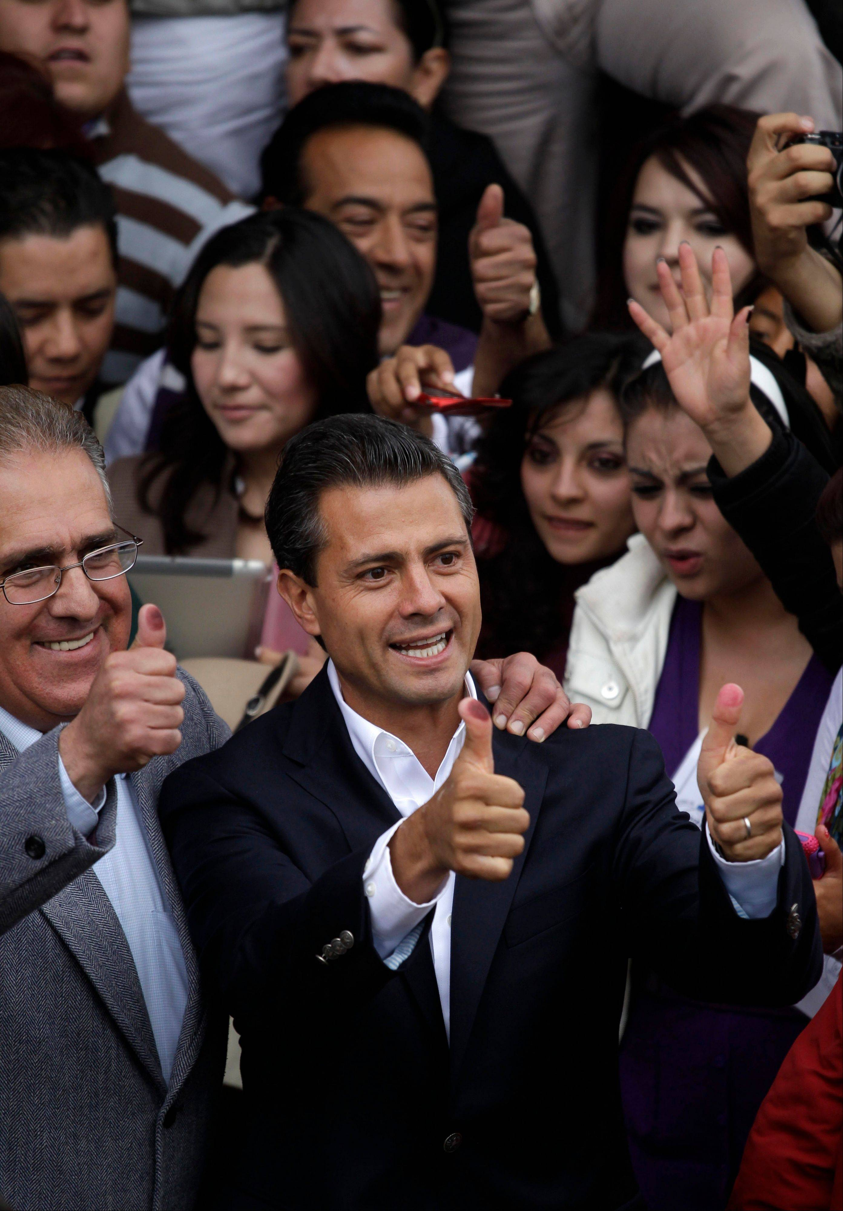 Enrique Pena Nieto, presidential candidate for the Revolutionary Institutional Party (PRI), shows his ink-stained thumbs after he cast his vote during general elections in Atlacomulco, Mexico, Sunday.