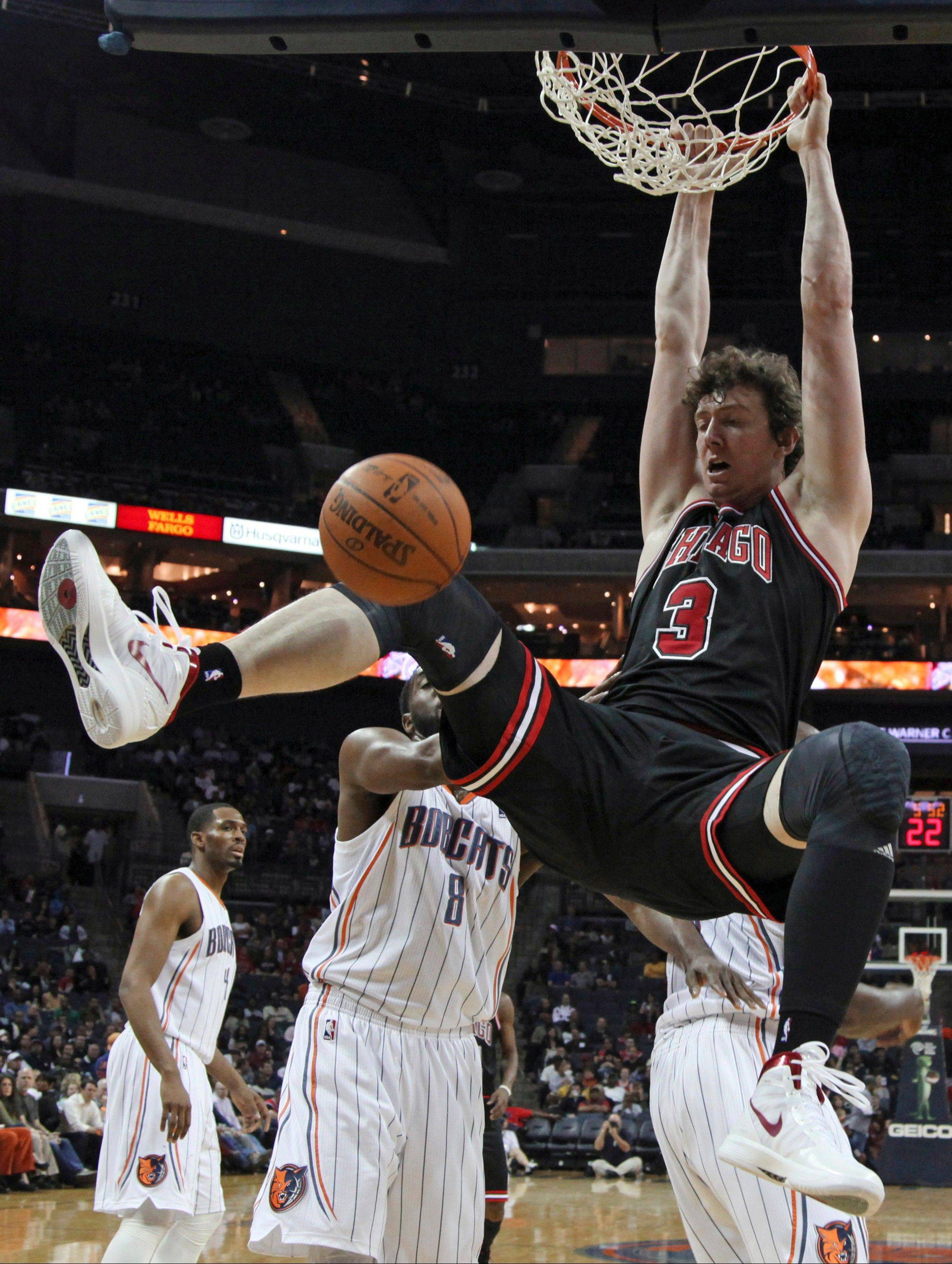 Omer Asik (3) dunks in front of Charlotte Bobcats' D.J. White (8) during the first half of an NBA basketball game in Charlotte, N.C., Wednesday, April 18, 2012. (AP Photo/Chuck Burton)