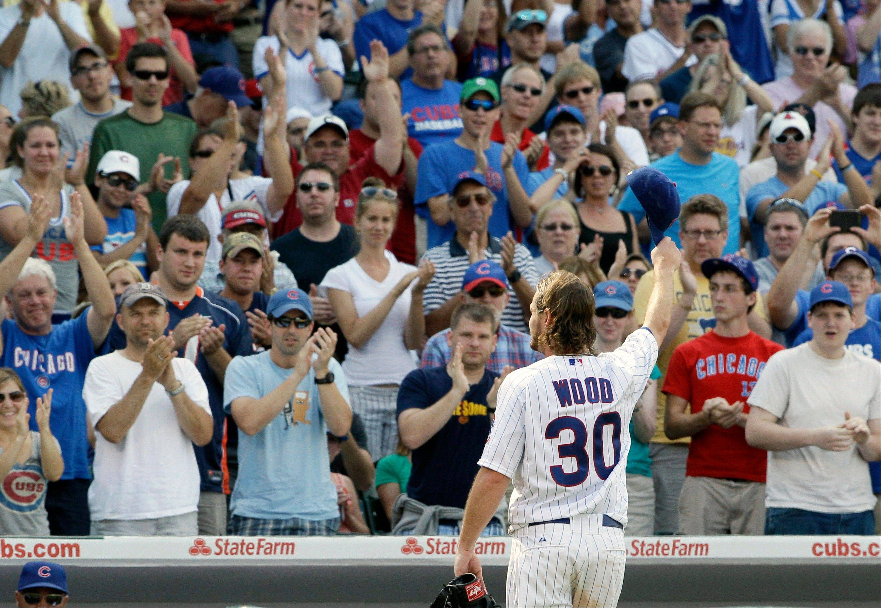 Travis Wood waves to the crowd as he walks back to the dugout after relief pitcher Shawn Camp replaced him during the eighth inning Sunday at Wrigley Field.