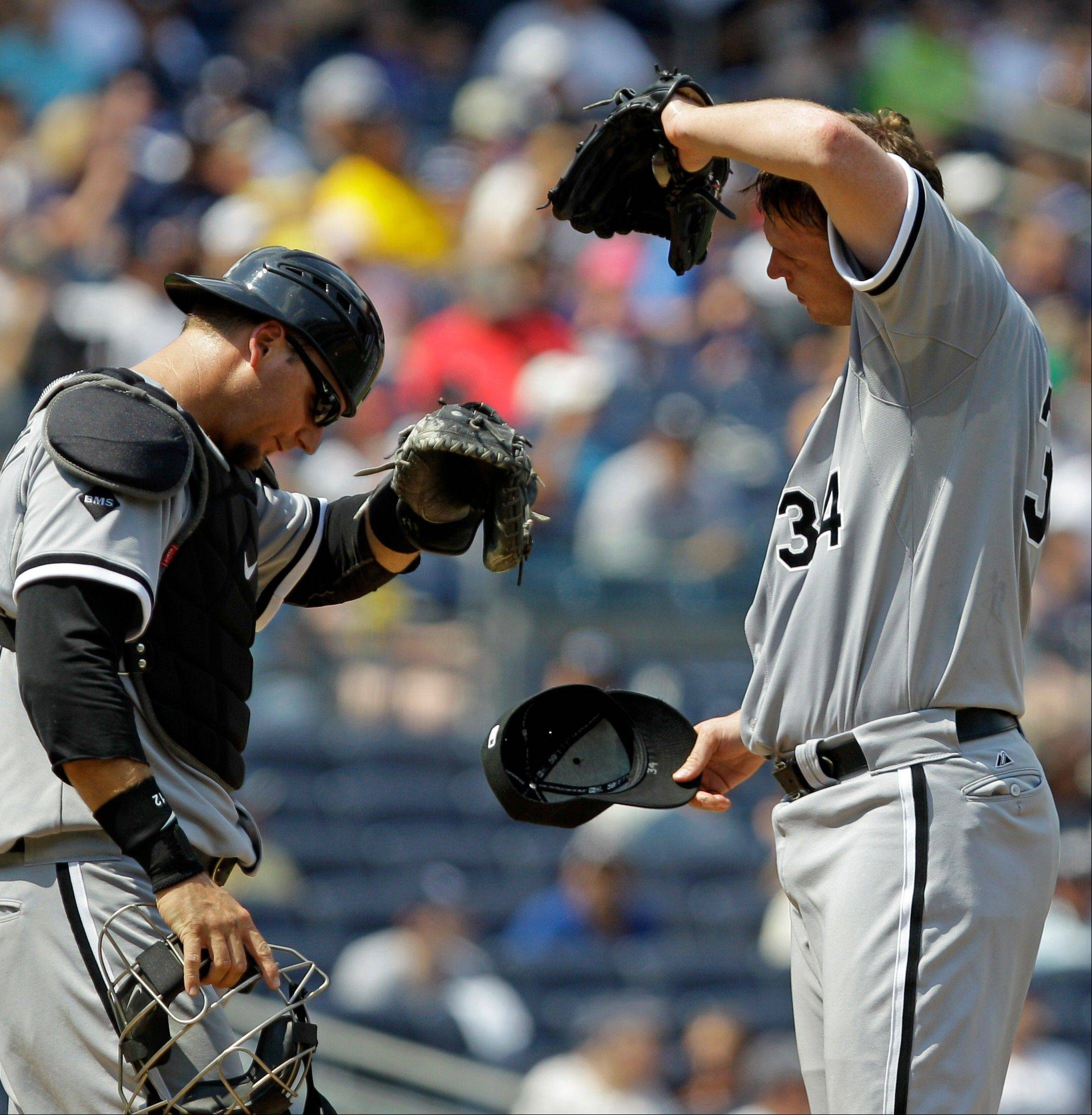 White Sox catcher A.J. Pierzynski, left, and starting pitcher Gavin Floyd wipe their brows amid the heat and humidity Sunday at Yankee Stadium.