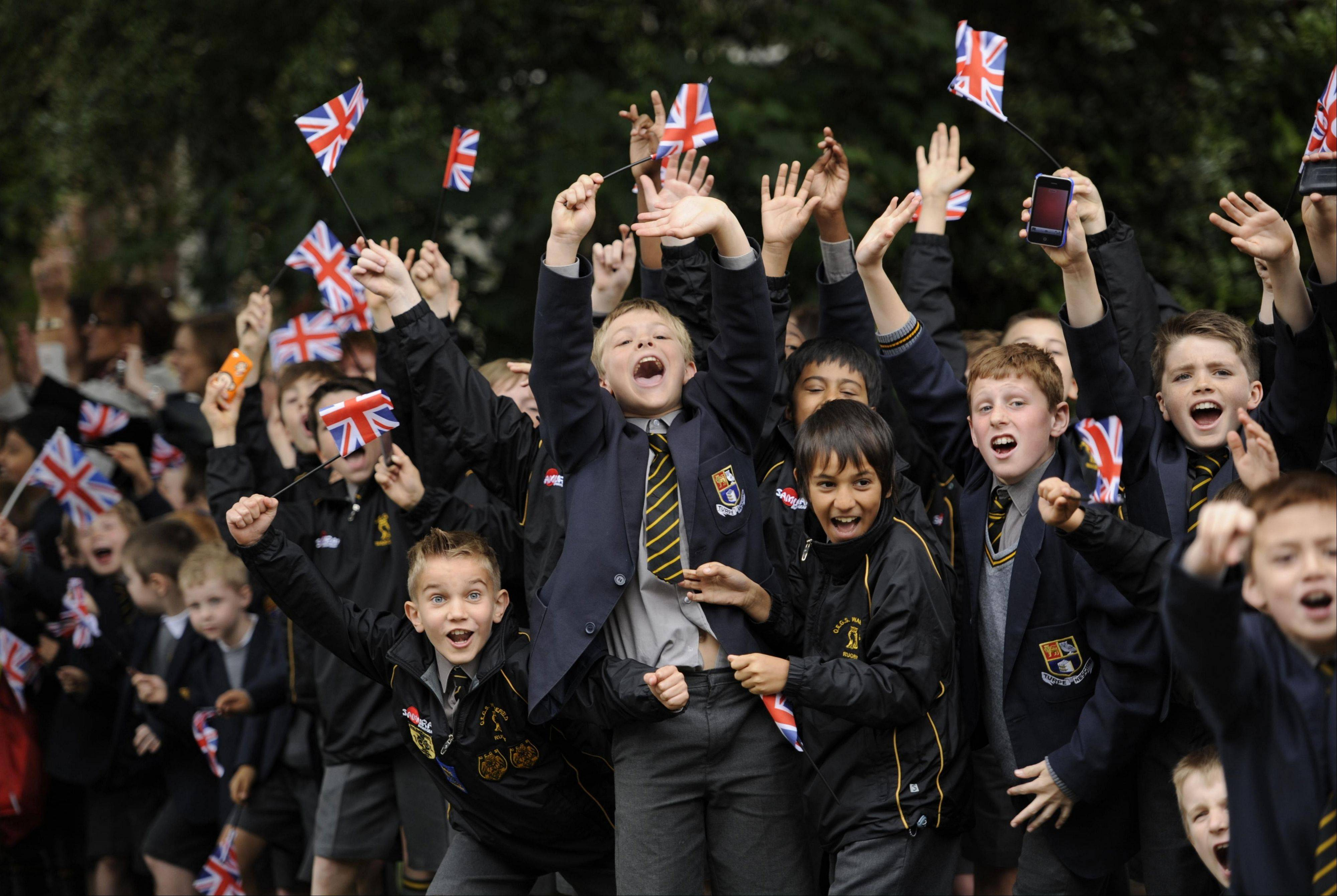 Local schoolchildren wave Union Jack flags as they cheer on the torchbearers in Wakefield, England.