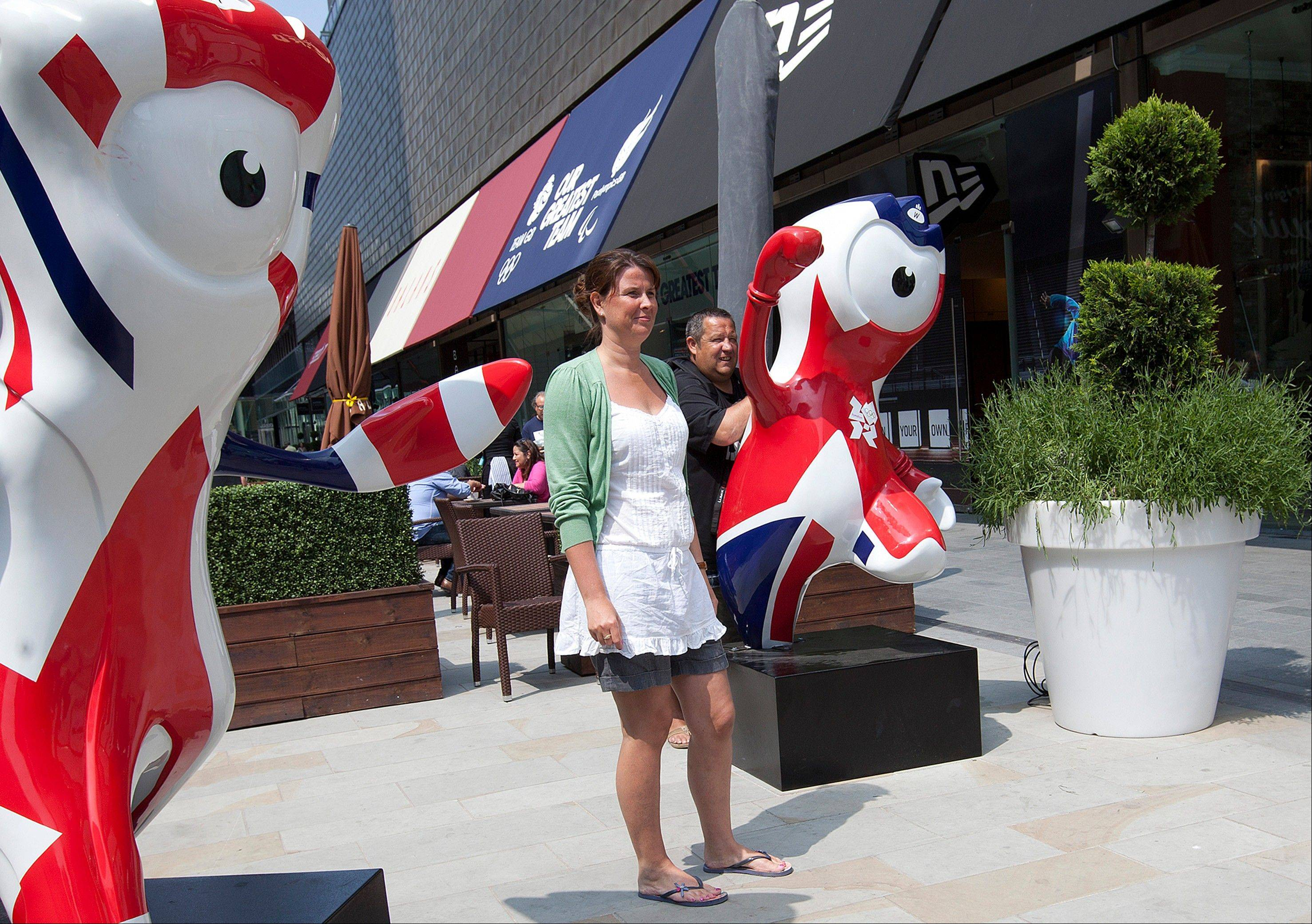 People pose for photographs beside the London 2012 Olympic Games mascots in a shopping mall next to the Olympic Park as final preparations are made ahead of the games in east London.