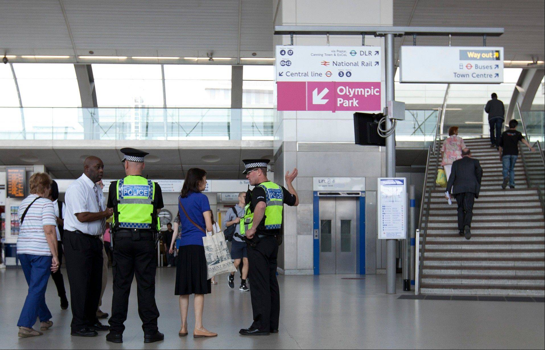 Police officers direct passengers beneath signs pointing to the Olympic Park, which are seen at the Stratford underground station as final preparations are made ahead of the London 2012 Olympic Games in east London.