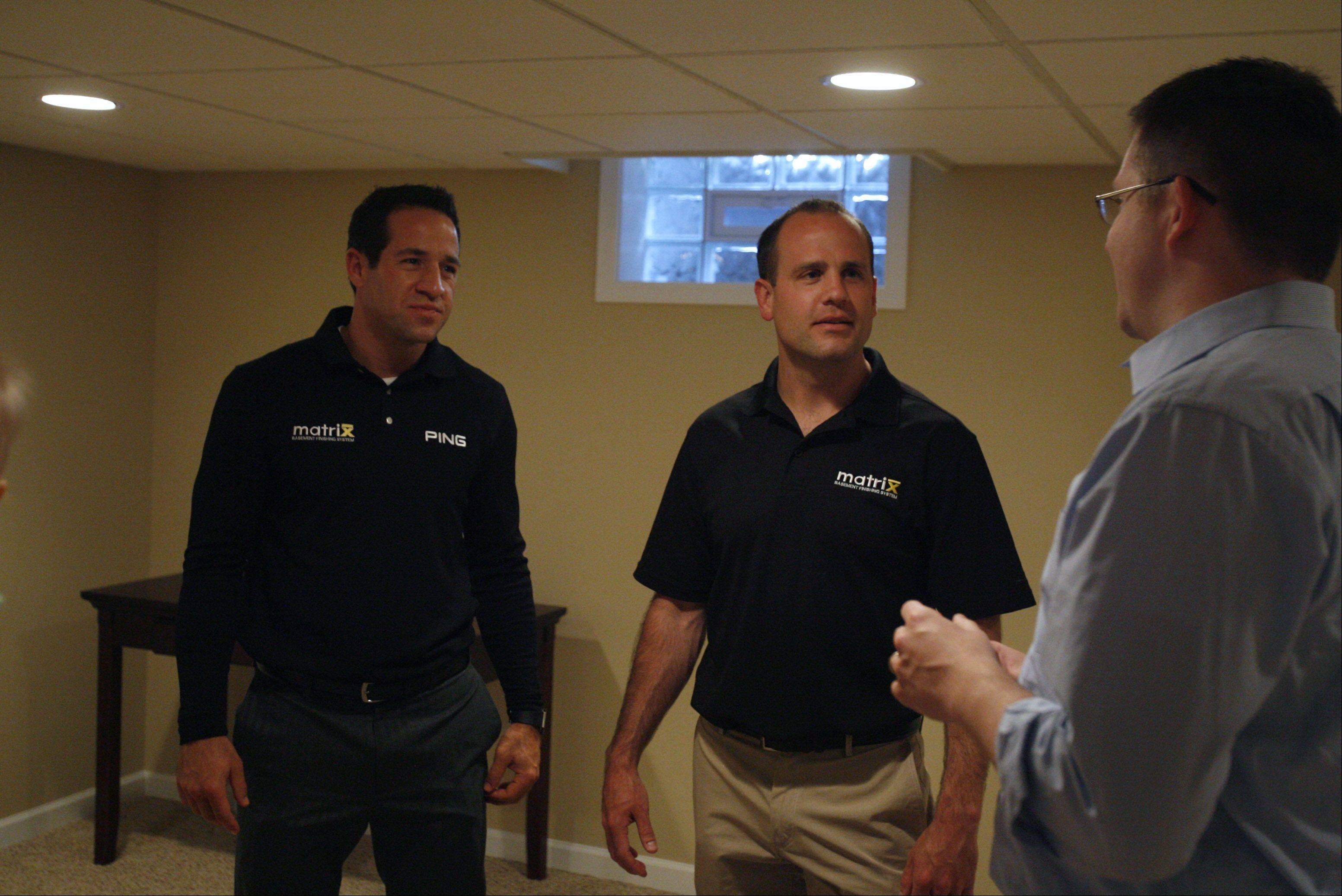 Matt Edwards, right, talks about his new basement with Matrix Basement Finishing System co-owner and president Nick Richmond, director of sales, left, and co-owner Brian Barrick.
