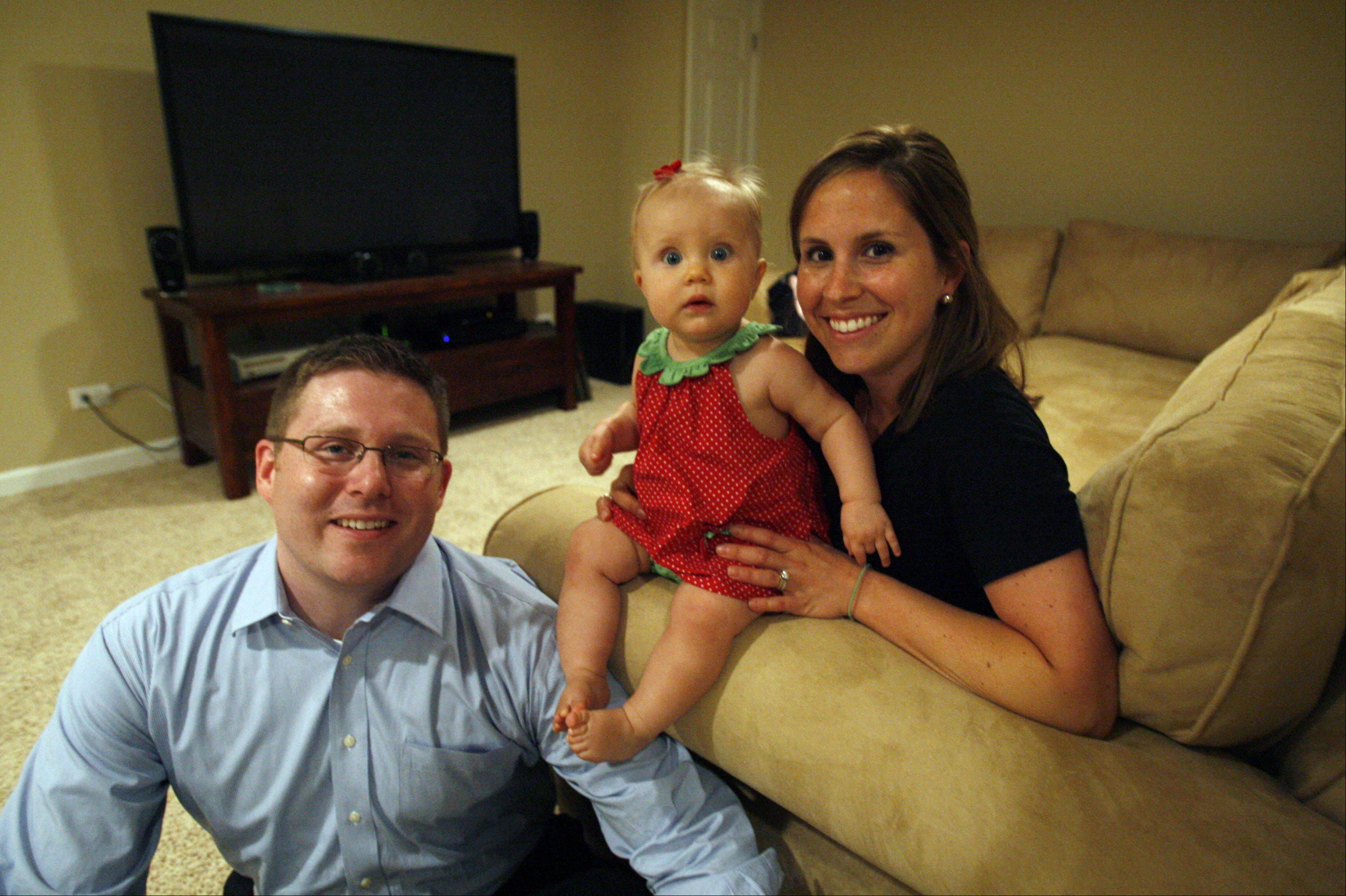 Ugliest Basement contest winners Matt and Anne Edwards with 10-month-old daughter Katherine in their newly finished basement in Arlington Heights.