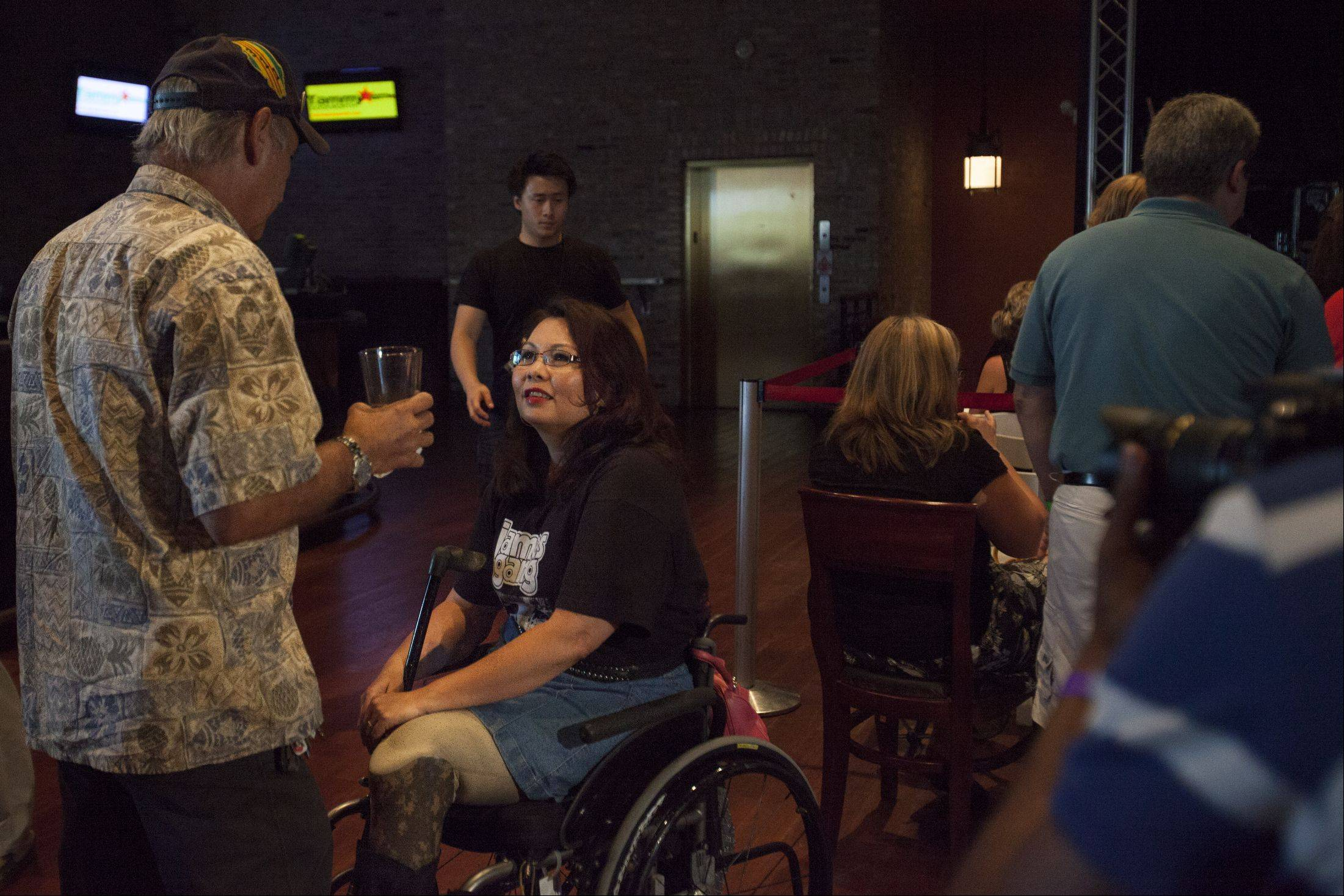 Joel Bissell/jbissell@dailyherald.comTammy Duckworth talks to volunteer and supporter Jim Garcia who is from Des Plains Legion Post 36 before Joe Walsh performed at John Barleycorn in Schaumburg for 500 Duckworth supporters.