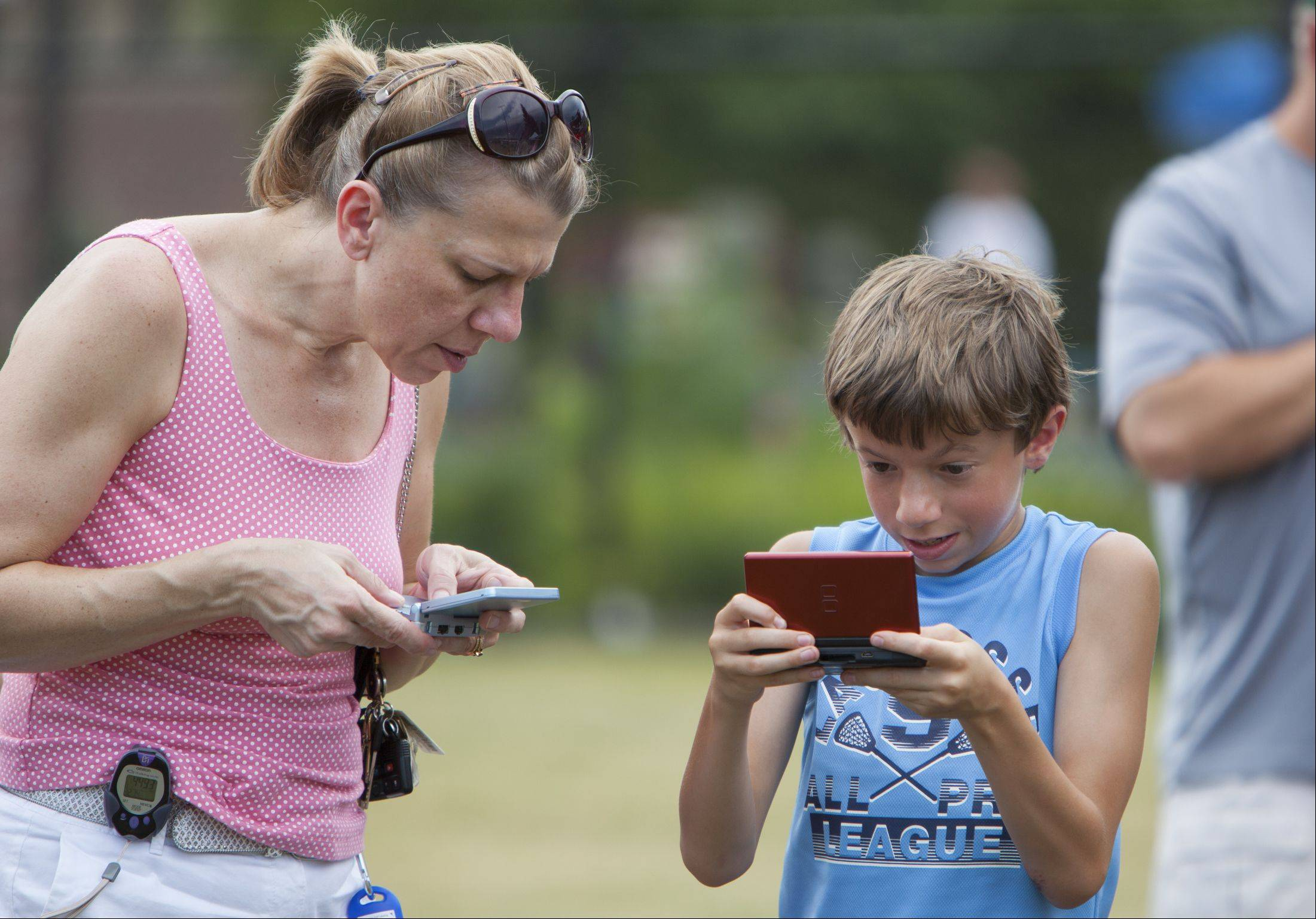 "Ten-year-old Michael Rossbach plays ""Rave Monster"" on his Nintendo DS as his mom, Dawn, plays a Super Mario game on her Nintendo Game Boy Advance SP in Palatine's Community Park on Sunday. They were part of a group that set a Guinness World Record for most people playing handheld video games together."