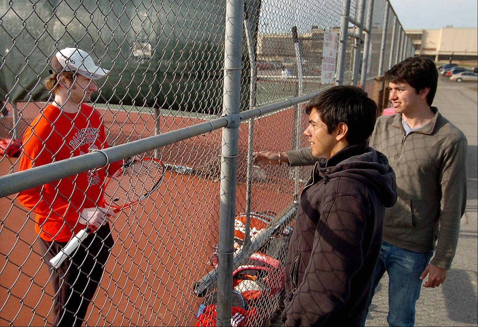 Rafael and Carlos Robles visit with Palatine tennis coach Jim Lange.