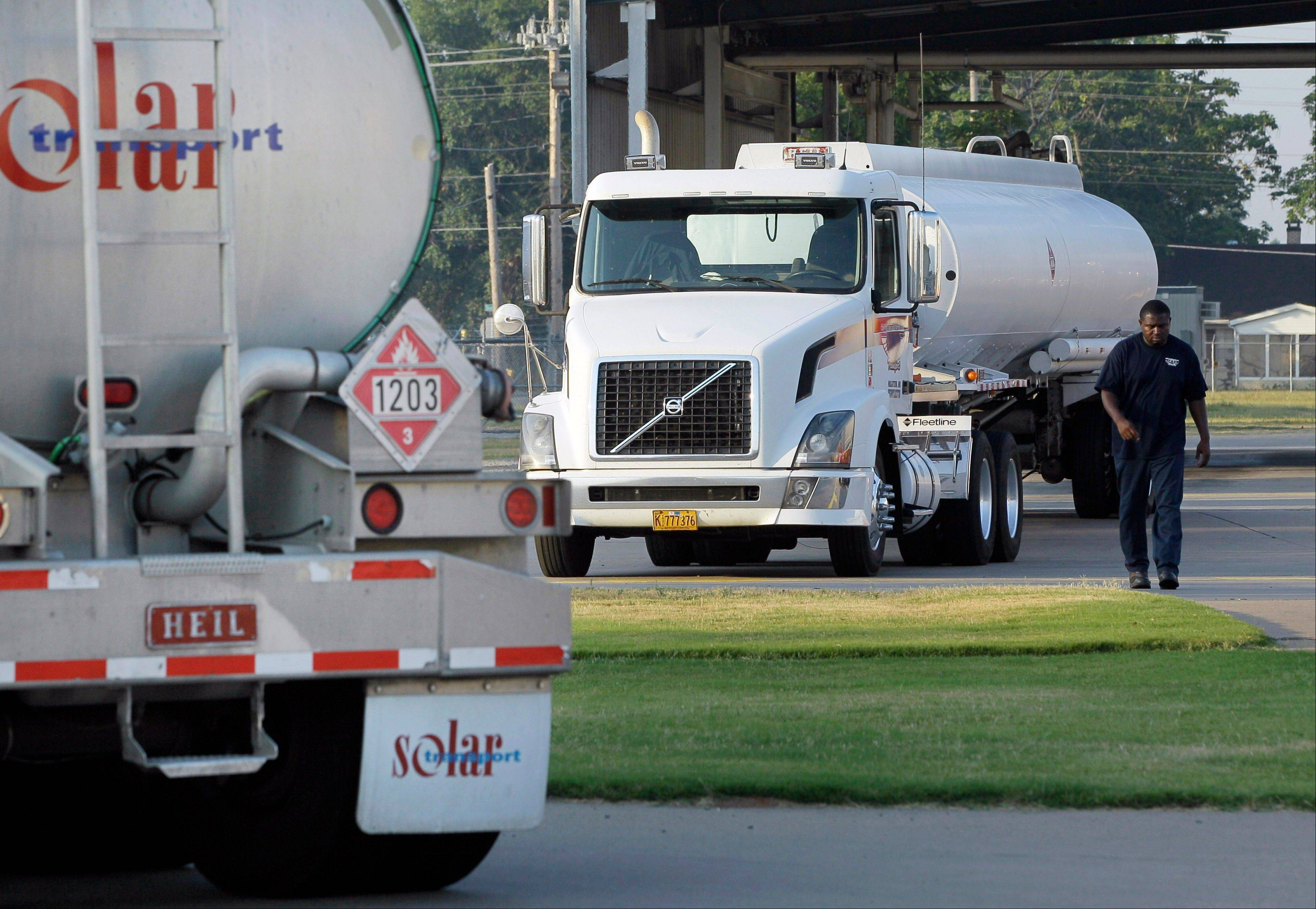 A man walks from a gasoline tanker truck at a North Little Rock, Ark., fuel distribution terminal.