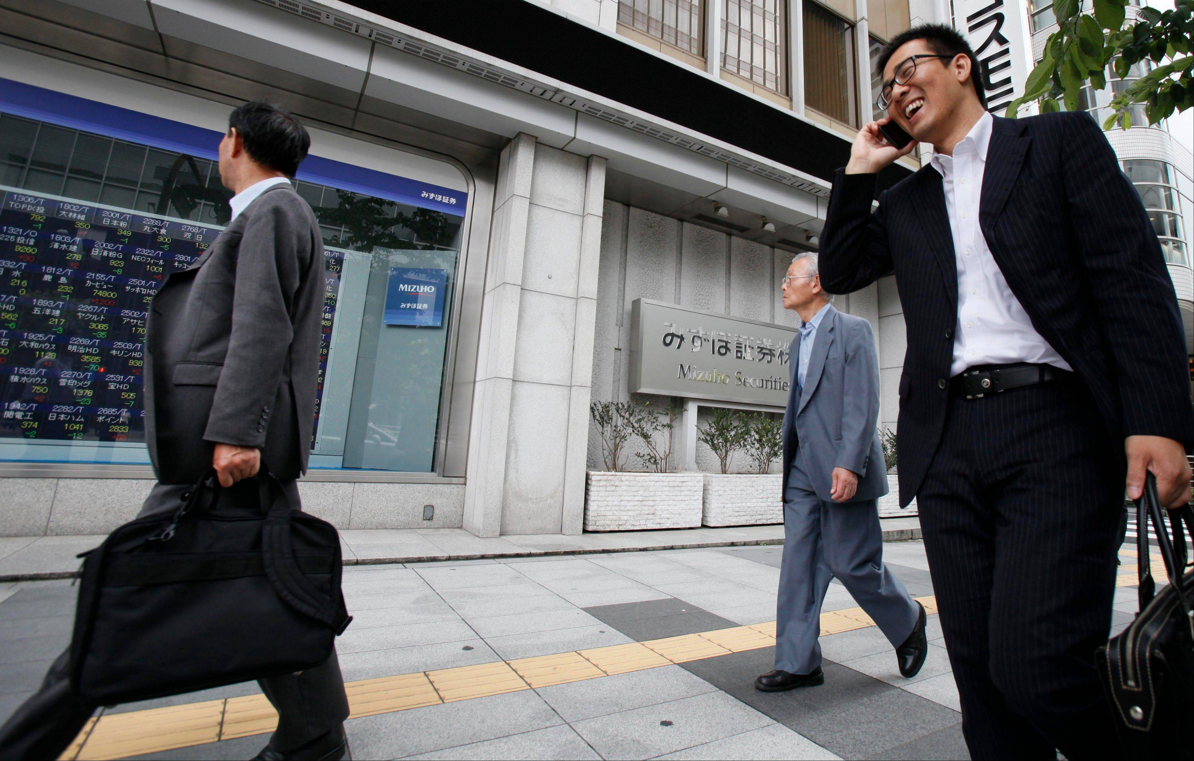 People walk past a digital display of Tokyo stock prices at a securities firm in Tokyo Monday.