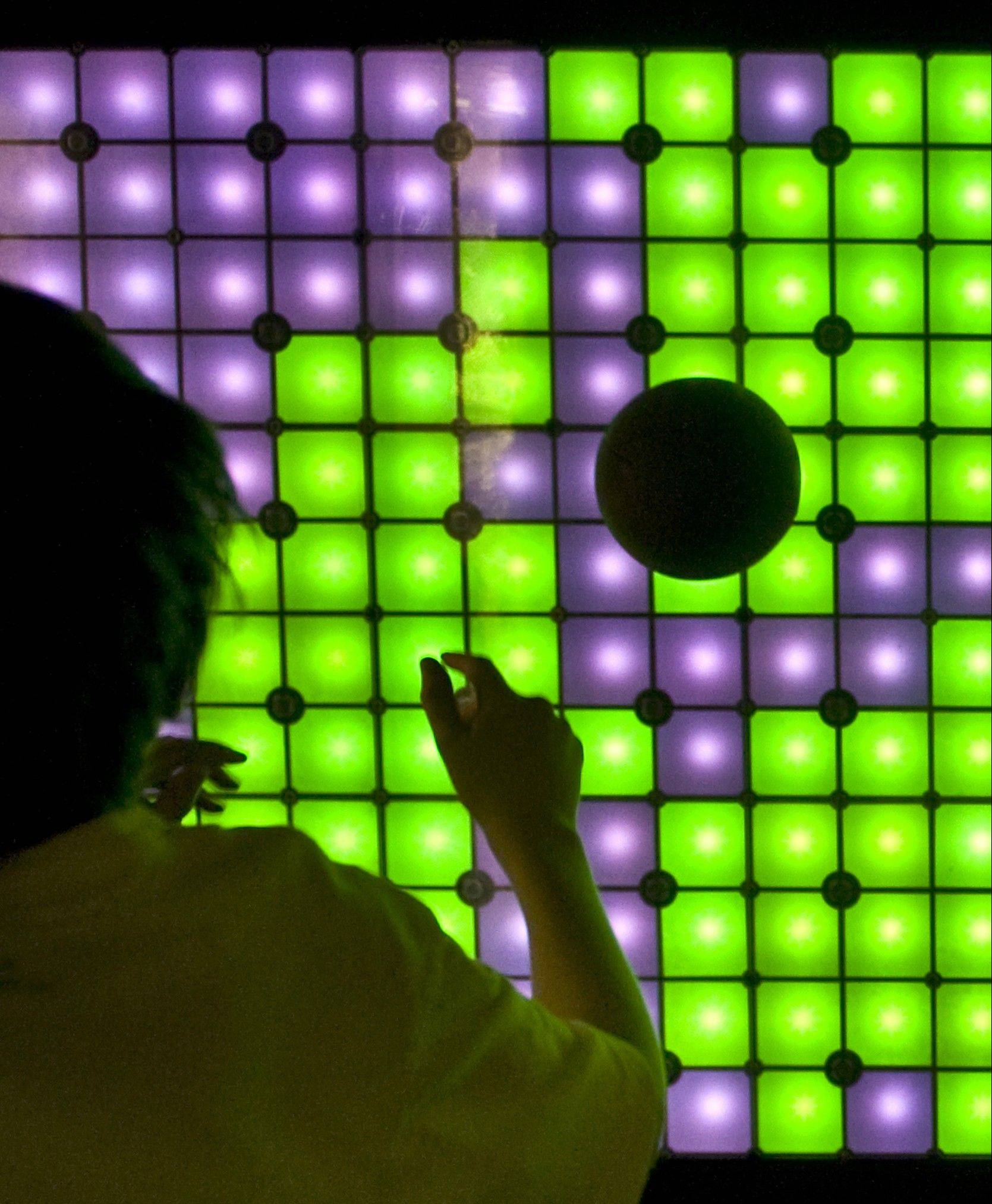Jake Eisenstat uses a medicine ball to turn purple lights green in a game called Splot.