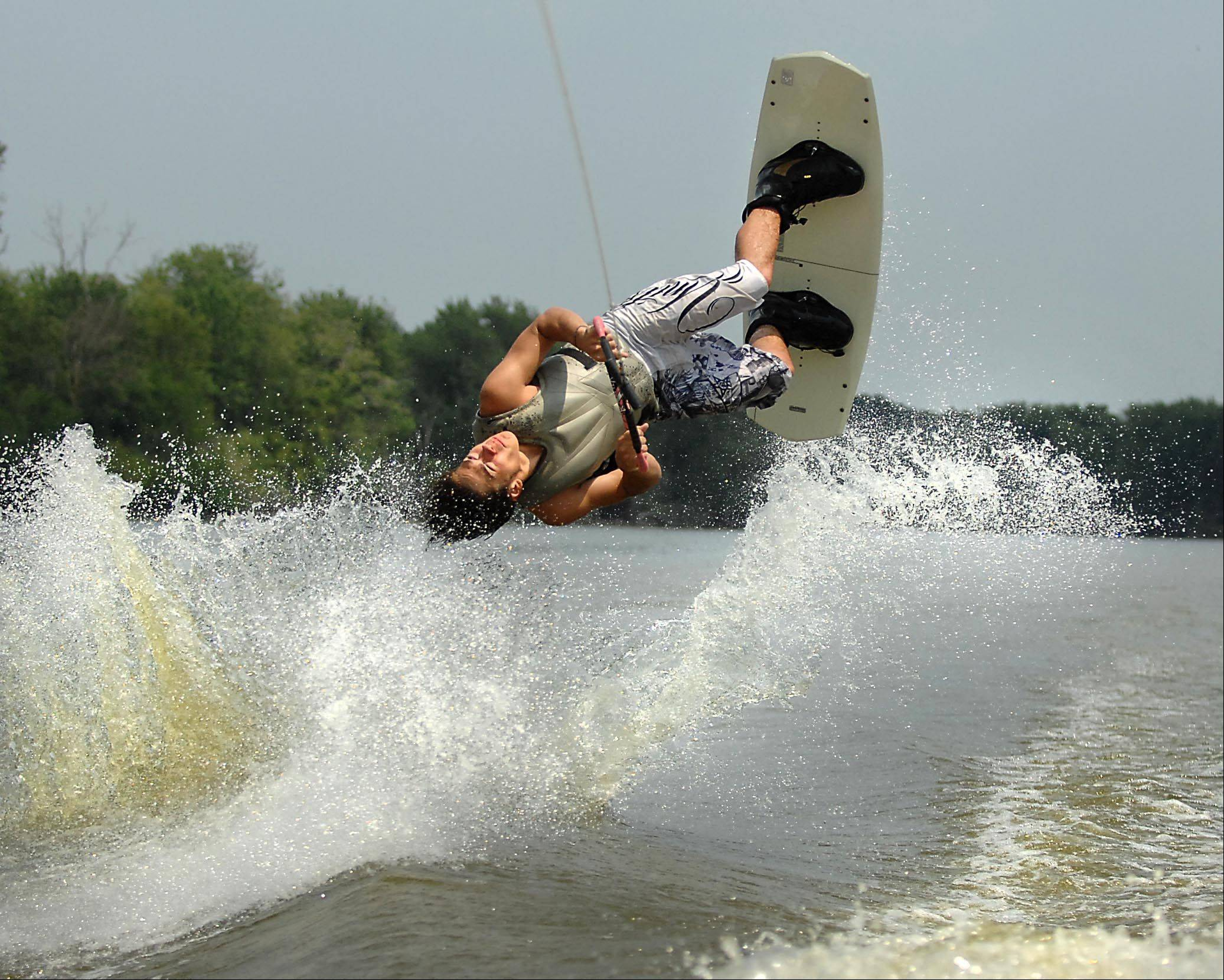 Xavier Contreras, 17, of Port Barrington, performs a roll as Keith Duck, owner of Raging Buffalo Wakeboard School, drives the boat on the Fox River near Cary Monday.