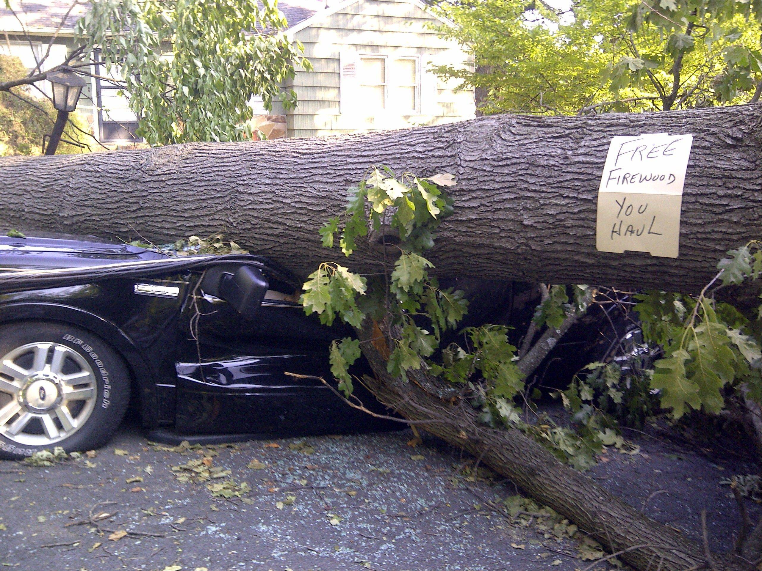 A tree sitting atop a vehicle offers free firewood in Falls Church, Va., Monday, as cleanup continued after Friday�s storm, Around 2 million utility customers are without electricity across a swath of states along the East Coast and as far west as Illinois as the area recovers from a round of summer storms that has also caused at least a dozen deaths.
