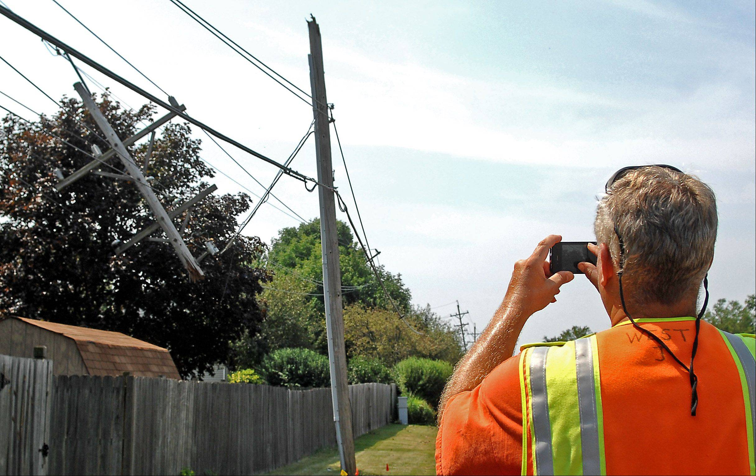 City of Batavia employee John West takes pictures of damage along Western Avenue Monday after a short but powerful storm did considerable damage in the Tri-Cities Sunday.