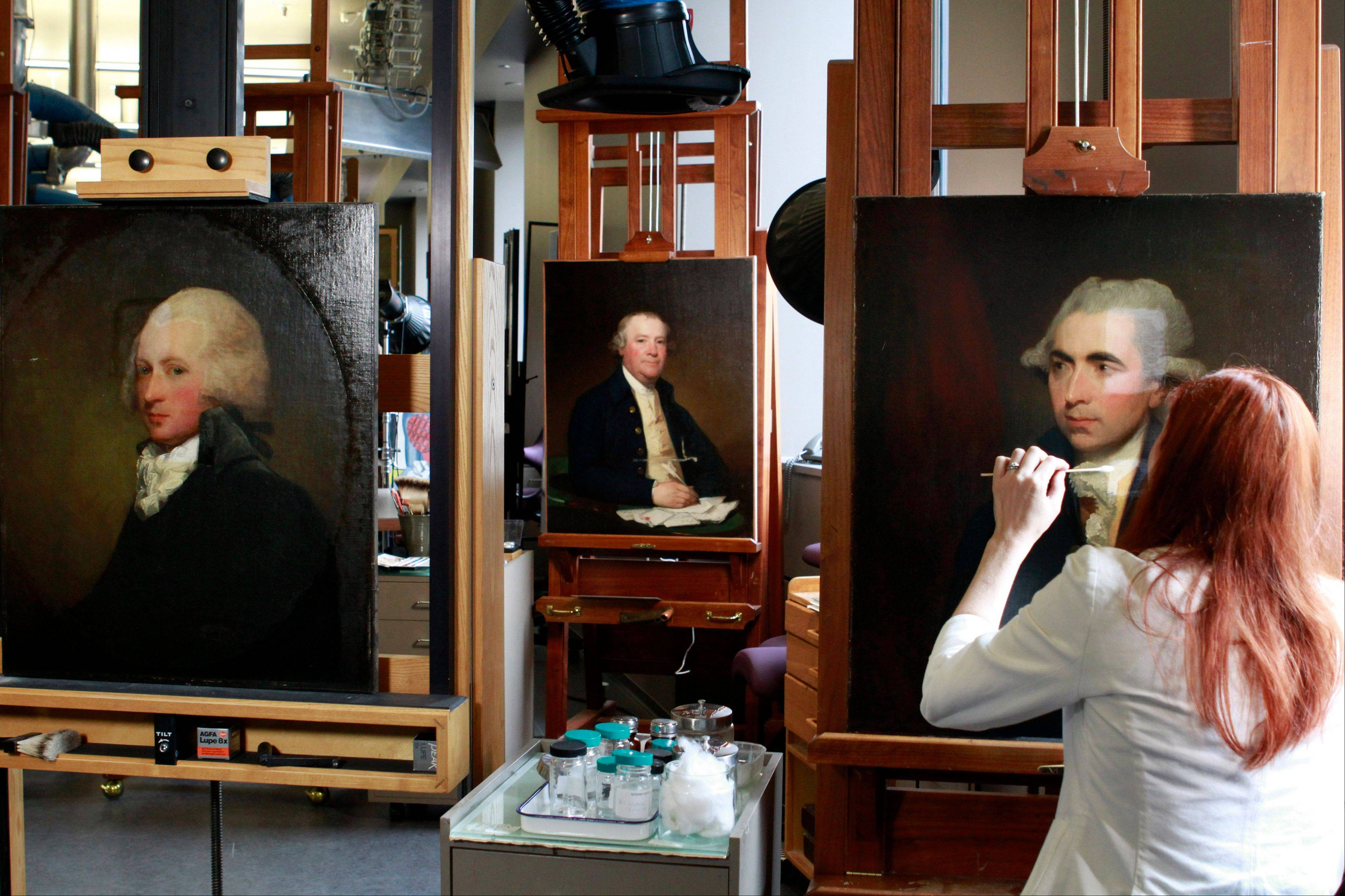 Painting conservator Joanna Dunn removes varnish, which had yellowed with age, as she restores a Gilbert Stuart painting of Luke White at the National Gallery of Art's Painting Conservation Lab in Washington.