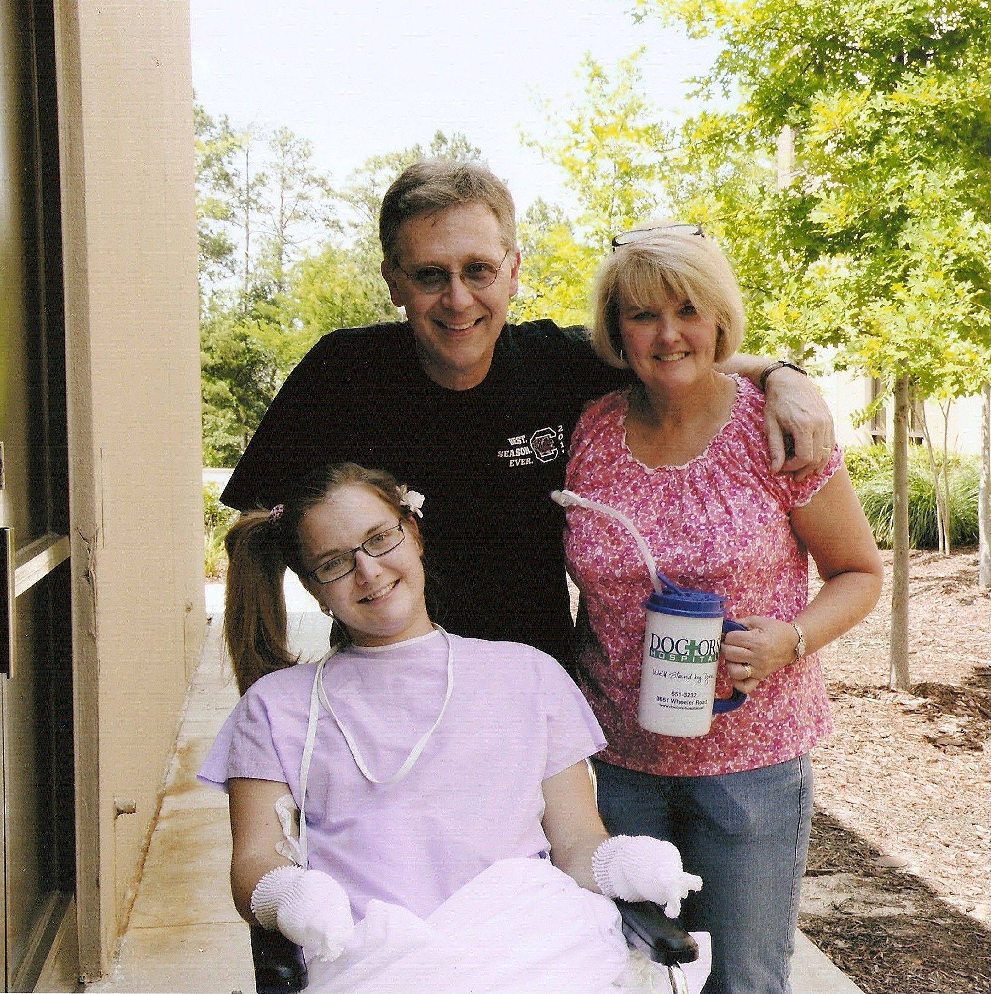 This Saturday, June 23, 2012 photo shows Aimee Copeland, left, with her parents, Andy and Donna Copeland, outside Doctors Hospital in Augusta, Ga.