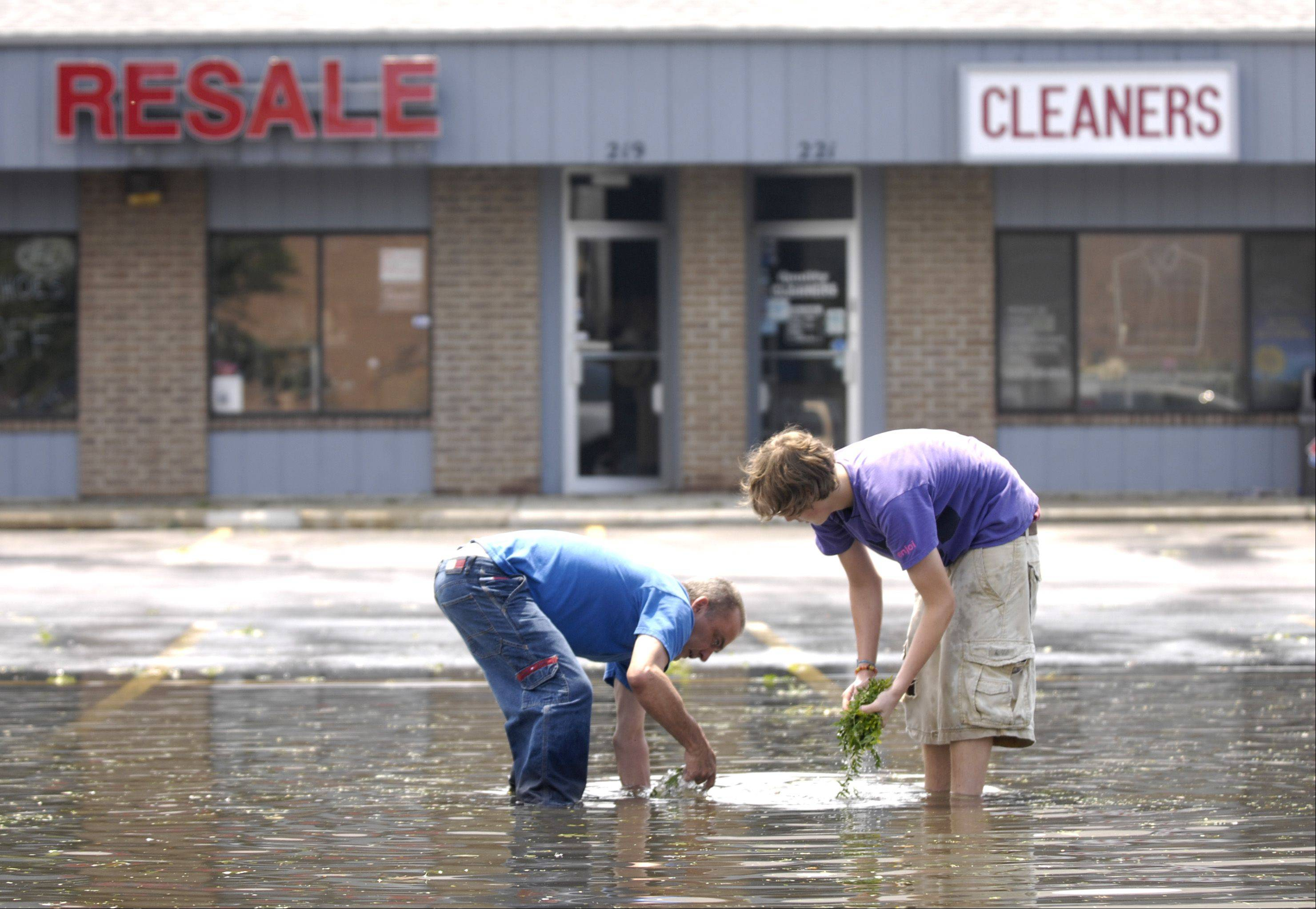 Bill Mein and Chase Wehle clear storm drains in the parking lot of a strip mall at the intersection of Geneva and County Farm Road in Winfield after an afternoon storm rolled through the western suburbs Sunday.