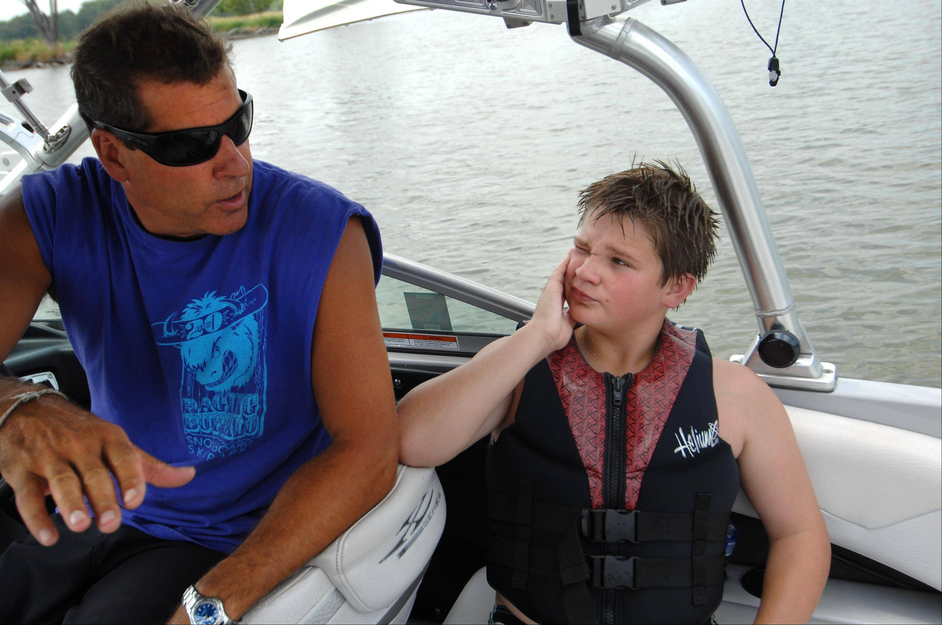 Keith Duck coaches Devin Patterson of West Dundee, as the 13-year-old takes a wake boarding lesson Monday on the Fox River near Cary. Duck operates the Raging Buffalo Wakeboard School during the summer season, and the Raging Buffalo Snowboard Park in Algonquin during the winter.