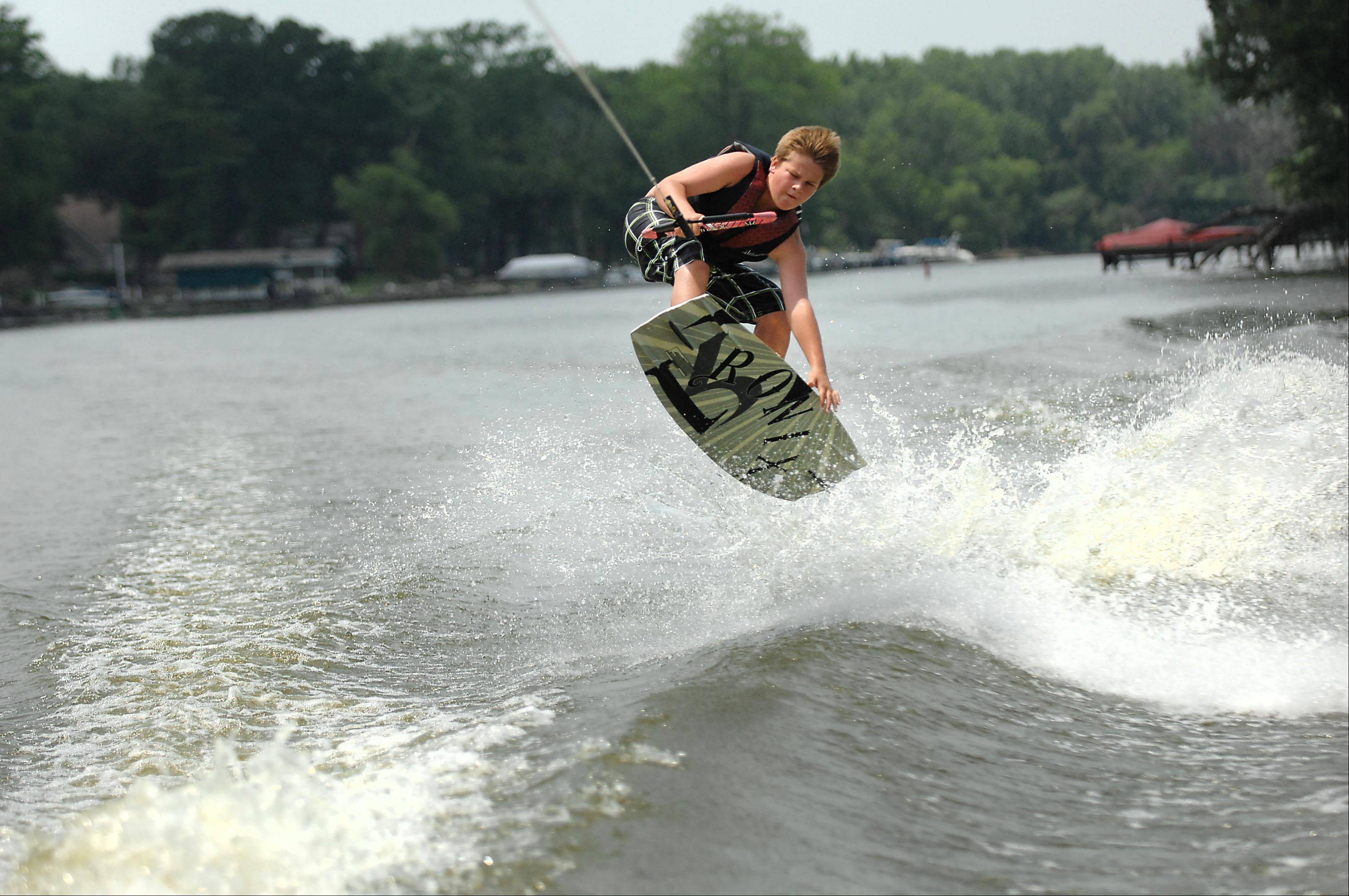 Devin Patterson, 13, of West Dundee, does a tail grab trick on the Fox River as Keith Duck drives the boat during his Raging Buffalo Wakeboard School lesson on the Fox River in Cary Monday.