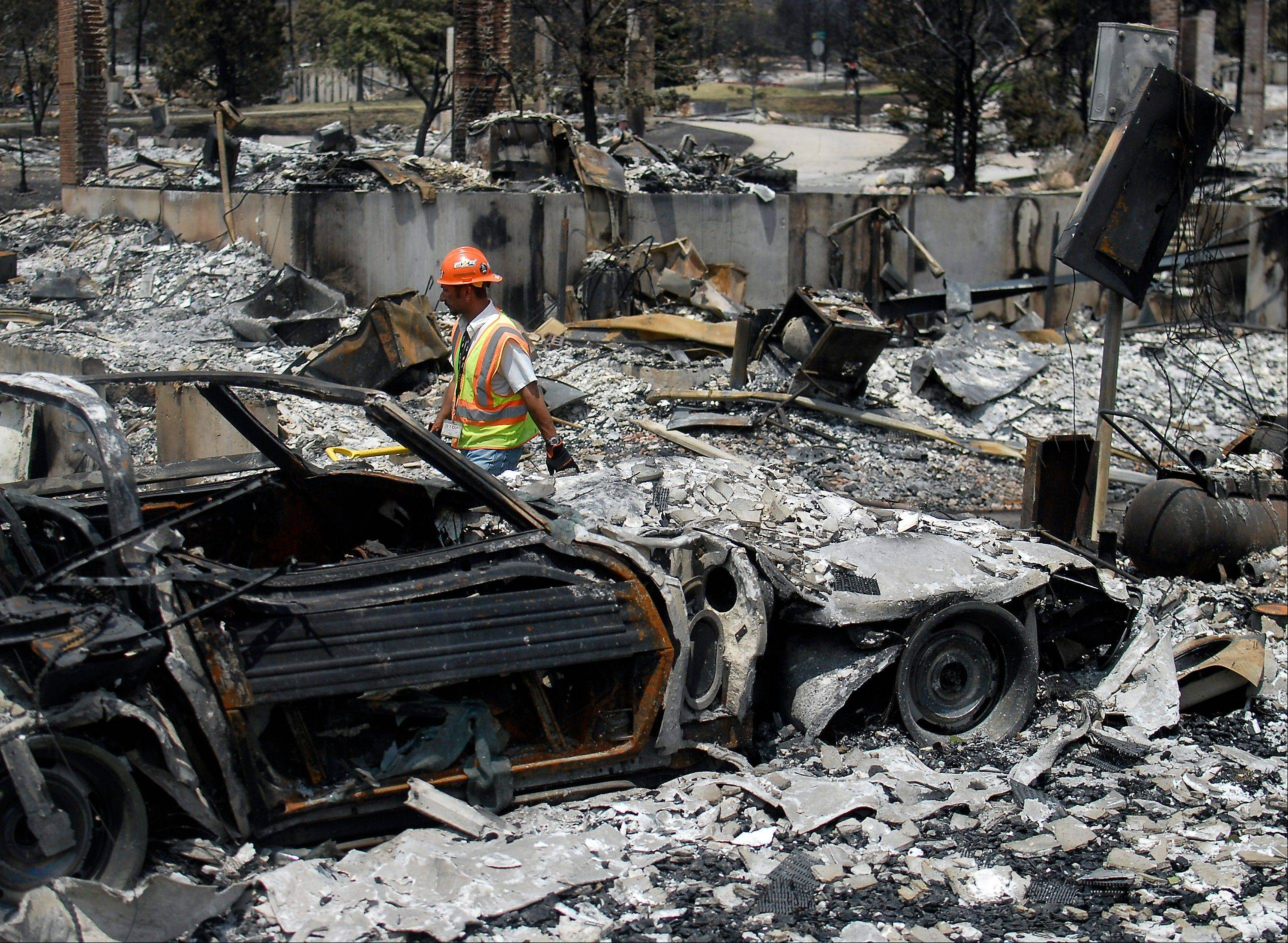 A utilities worker walks through homes destroyed by the Waldo Canyon Fire in the Mountain Shadows neighborhood of Colorado Springs, Colo., Monday. The blaze, now 45 percent contained, has damaged or destroyed nearly 350 homes.
