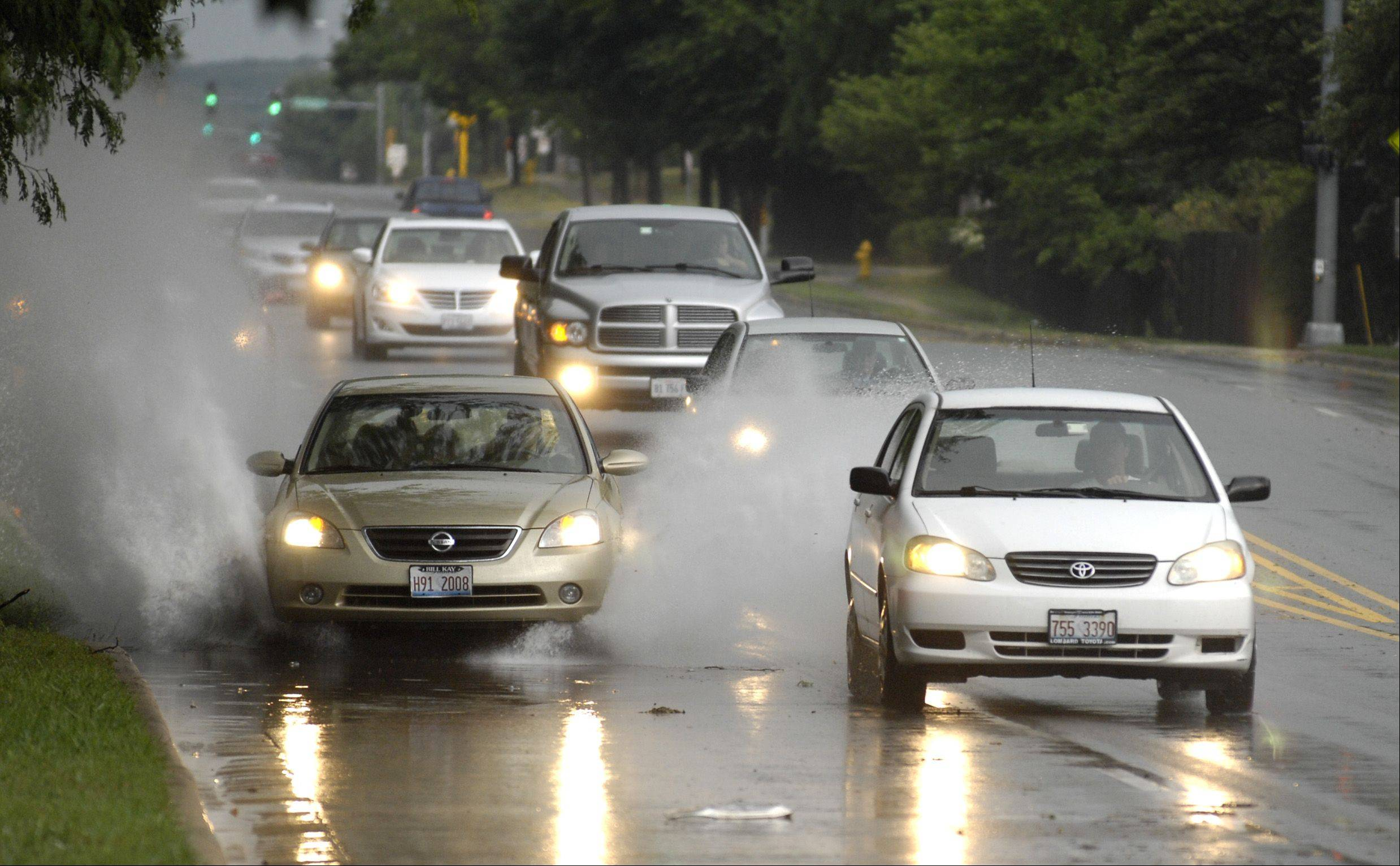 Cars drive through some water along Naperville Road in Wheaton after an afternoon storm rolled through DuPage County, Sunday.