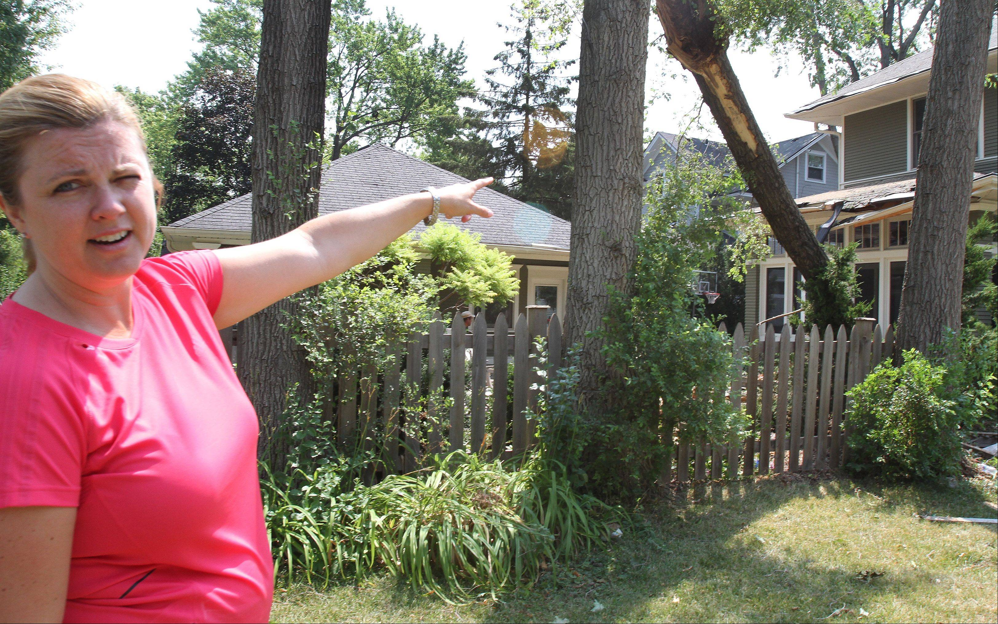 Sarah Bowers points to the damage done on her house in the 200 block of West Jefferson in Wheaton after Sunday's storm. She was not home at the time, but her husband and son were. They were able to get it cleaned up quickly on Monday morning.