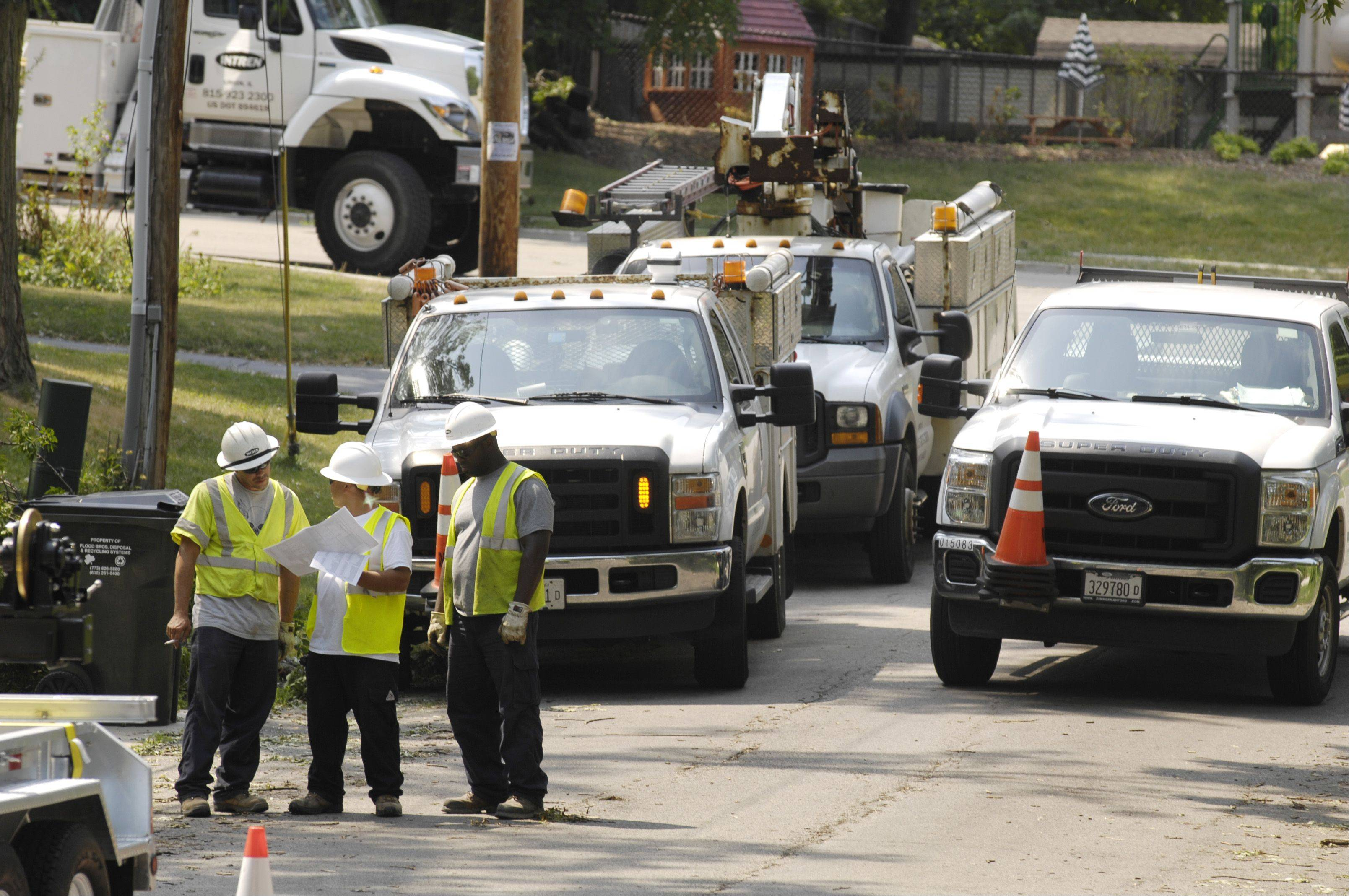 Utility crews work in Wheaton to restore services after a Sunday afternoon storm rolled through DuPage County knocking out power to tens of thousands.
