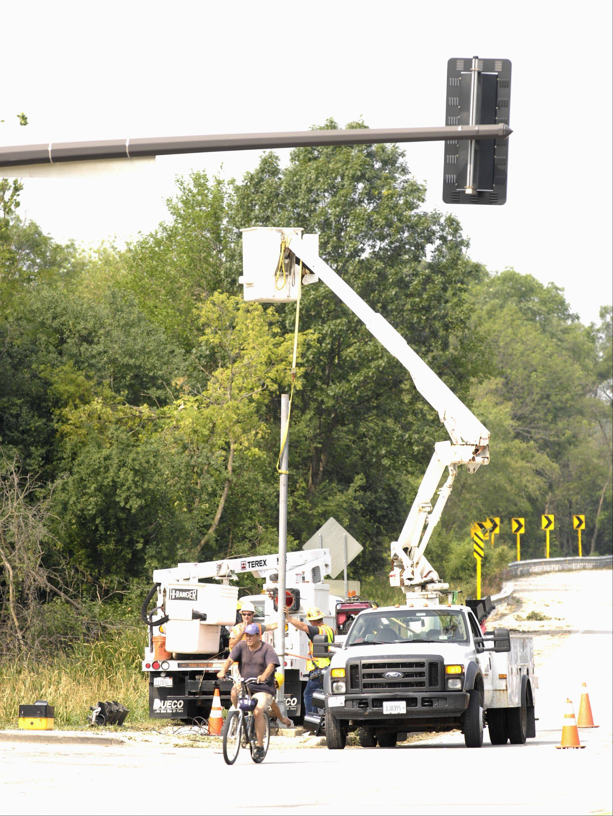 Crews work to repair a traffic signal at the intersection of Winfield and Geneva Road, Monday morning after a storm rolled through DuPage County, Sunday.