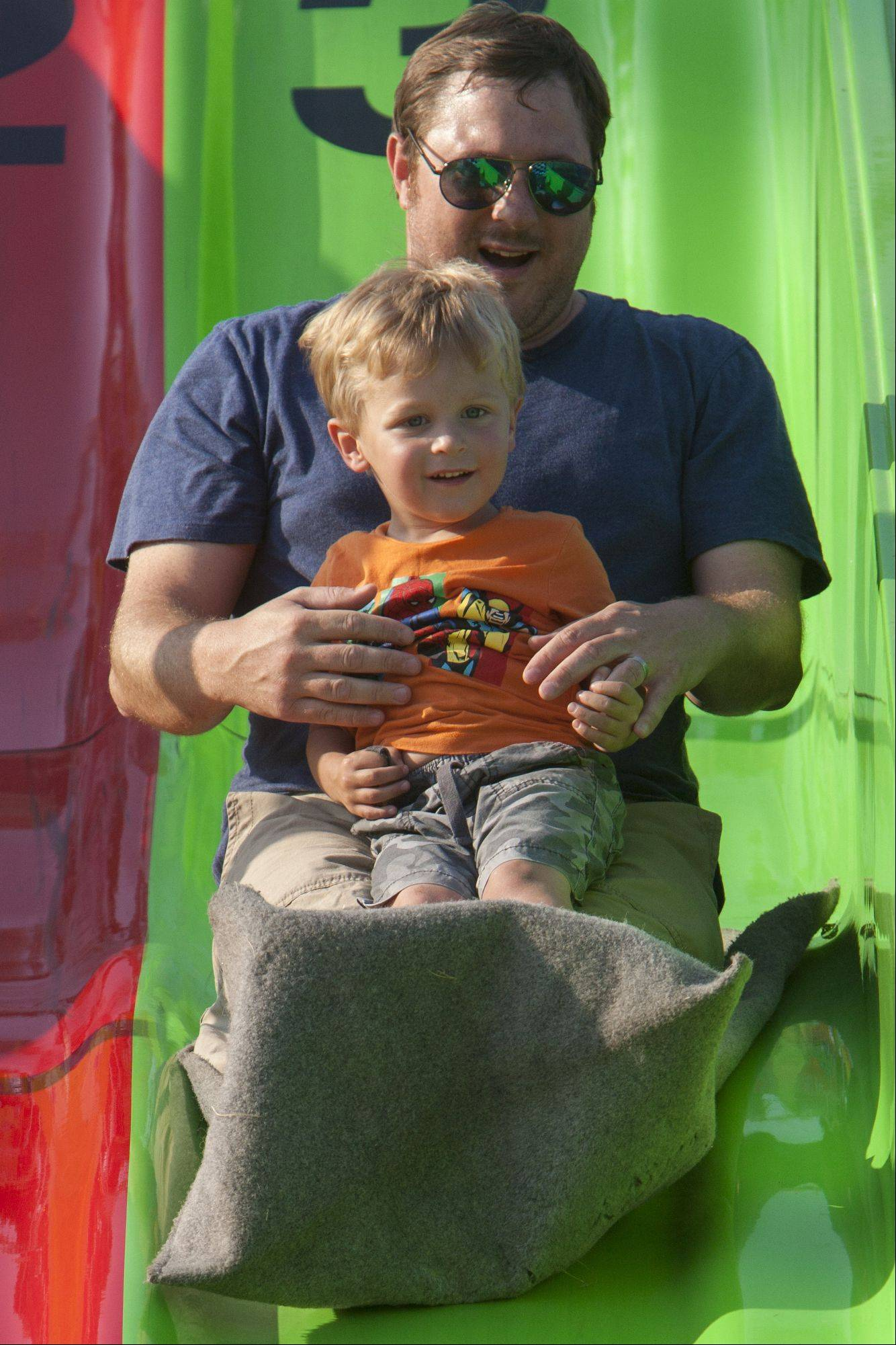 Tim Crenshaw and his son Jimmy, 3, of Mundelein, slide down a fun slide at Mundelein Community Days.