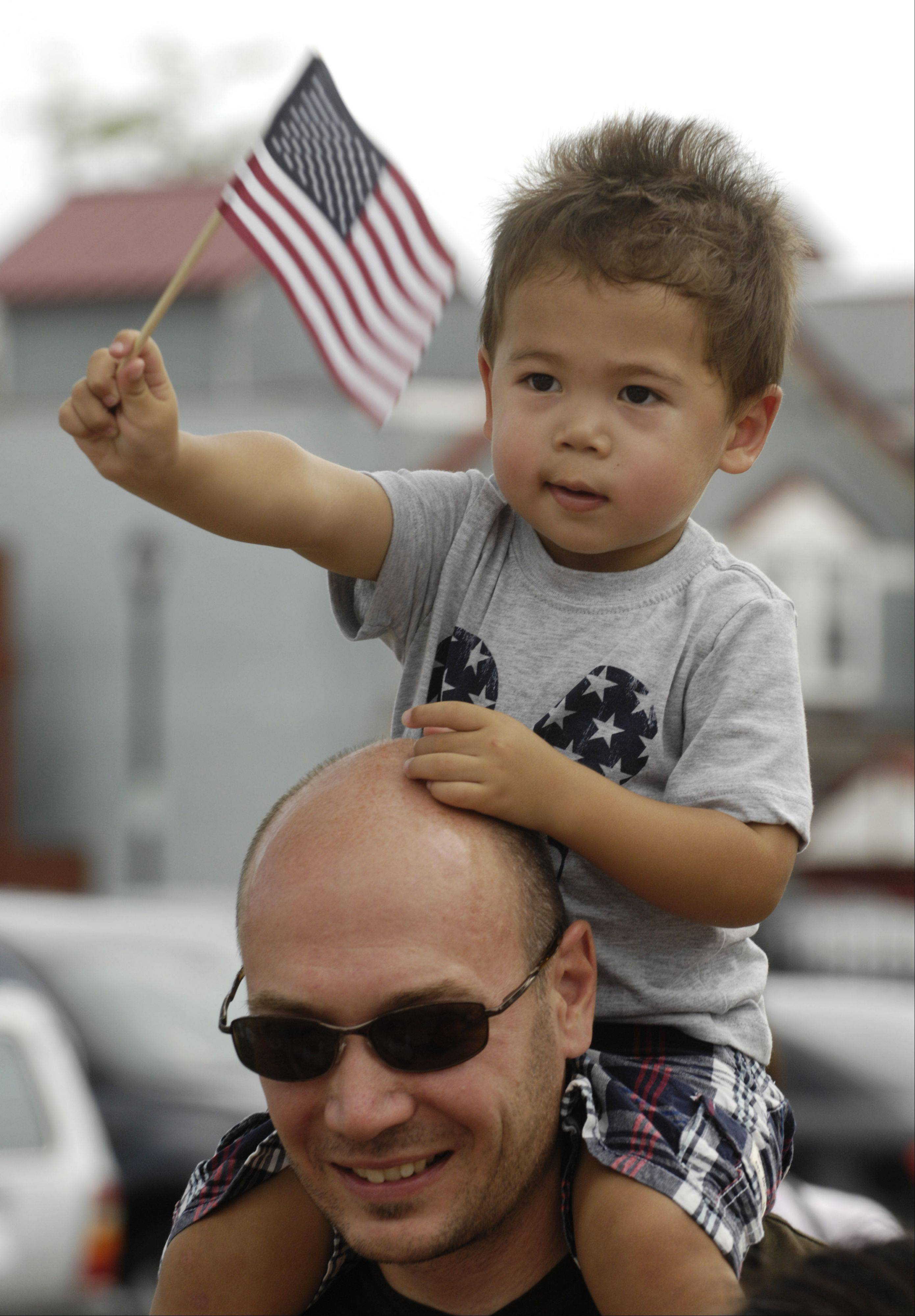 Nathan Haulotte, 2, of Palatine, waves his flag while riding the shoulders of his dad, Andrew, during the Palatine Hometown Parade Saturday.
