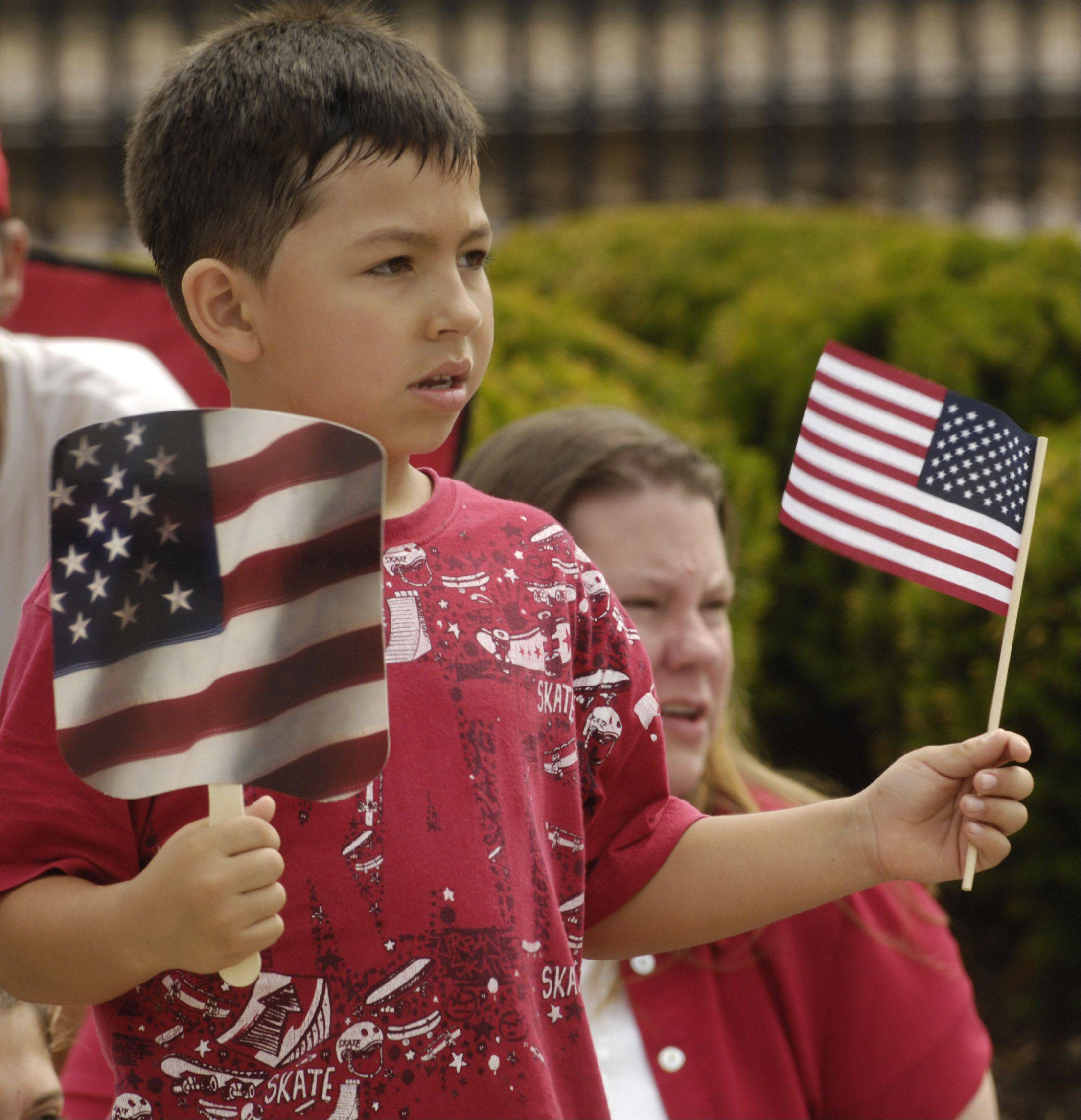 J.J. Islas, 6, of Palatine, cools himself with a fan held in one and hand and waves a flag with the other hand during the Palatine Hometown Parade Saturday.