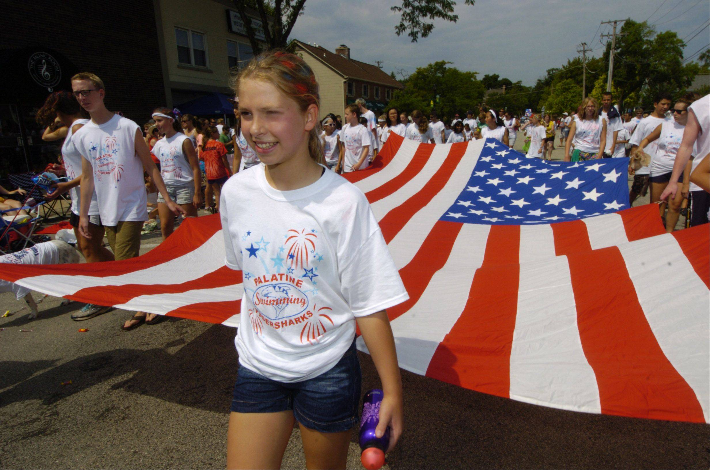 Michala Kueker, 11, of the Palatine Tiger Sharks swim team helps carry a large American flag during the Palatine Hometown Parade Saturday.