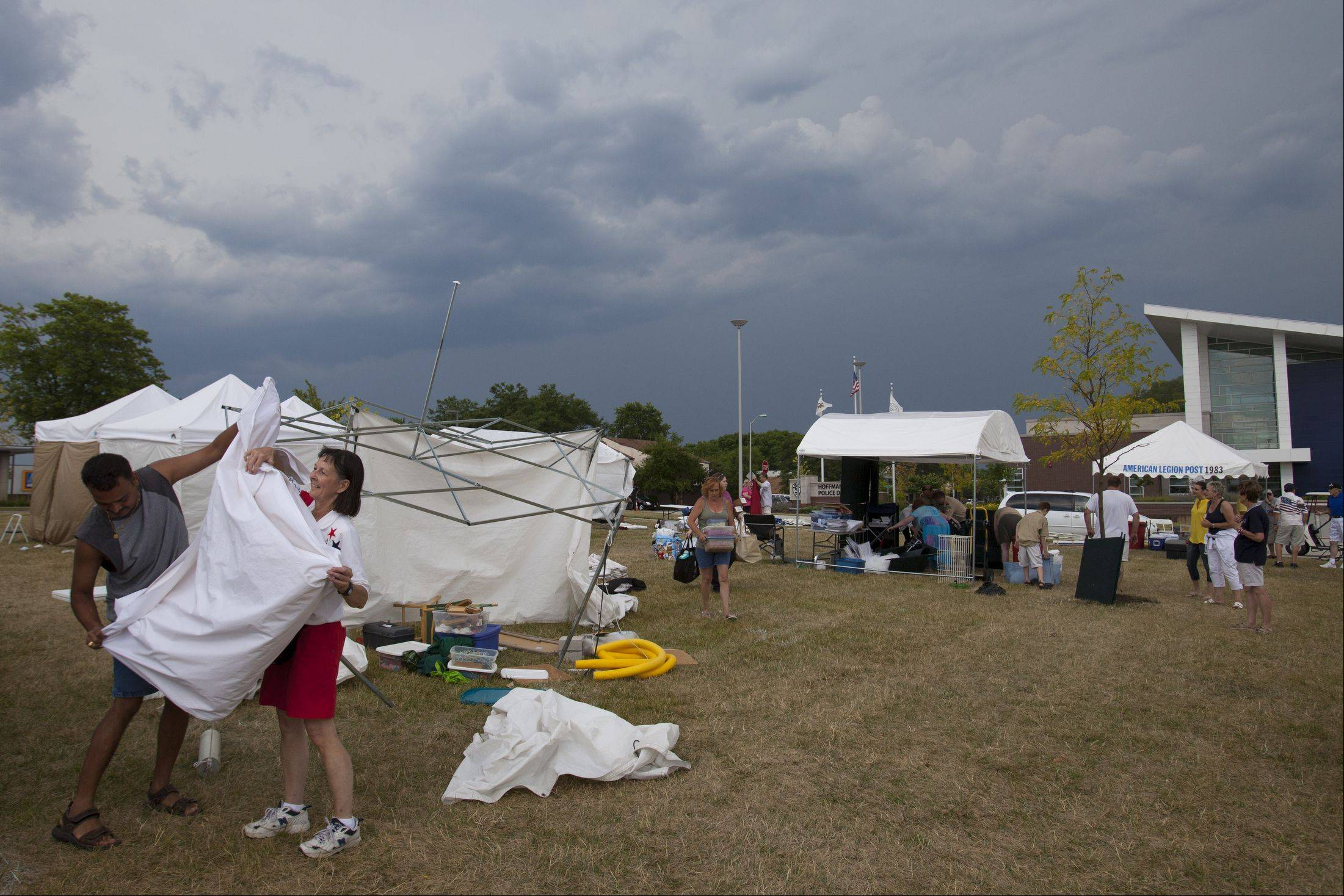 Amit Patel of Hoffman Estates helps Cyndy Jirsa of Schaumburg after strong winds blew over her tent and damaging about 50% of her wood crafts including: bird houses, key holders, and paper towel holders at the Hoffman Estates Arts and Crafts Fair.