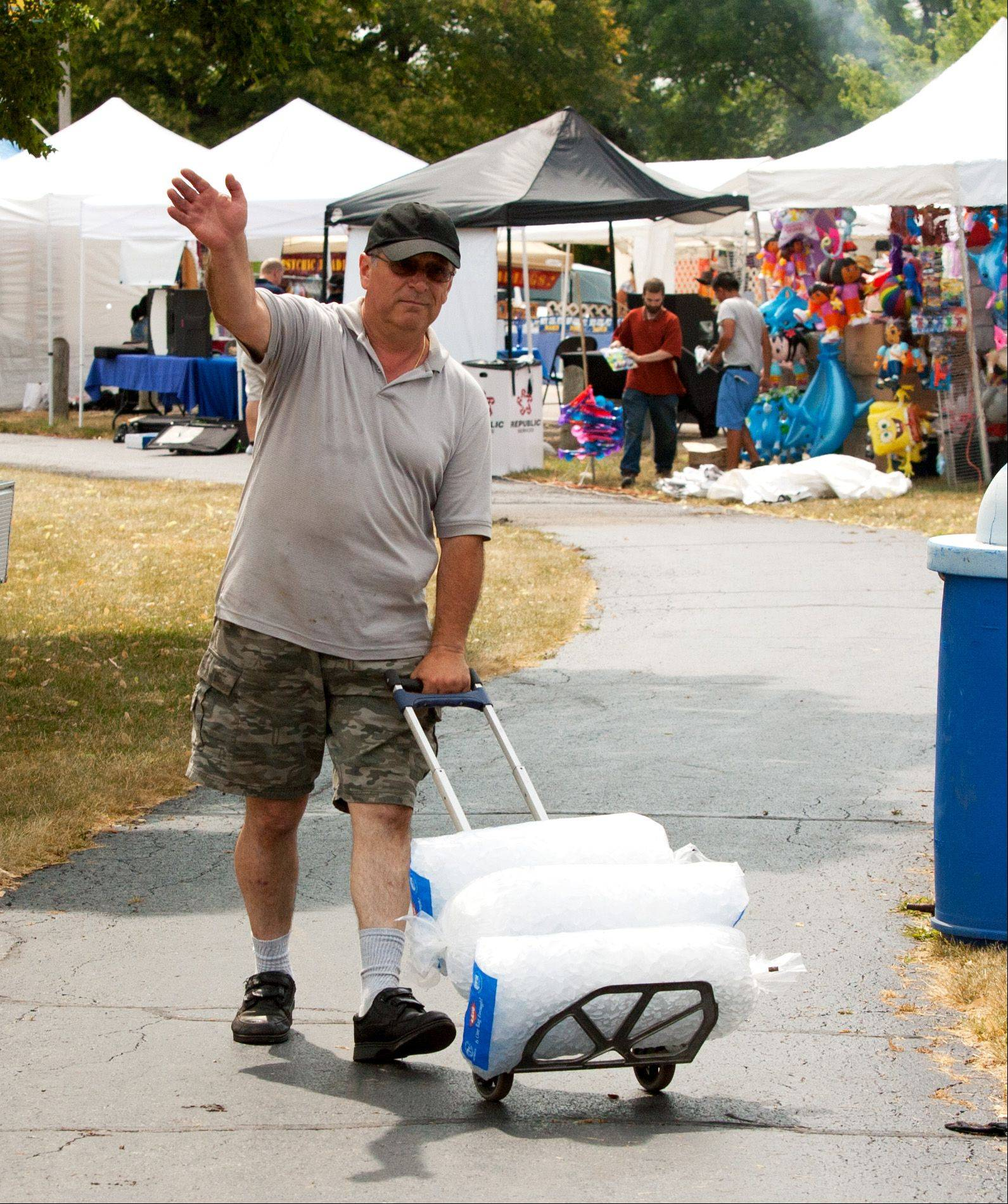 Vendor Frank Michaels carts ice to his booth, during the Eyes to the Skies Festival in Lisle.
