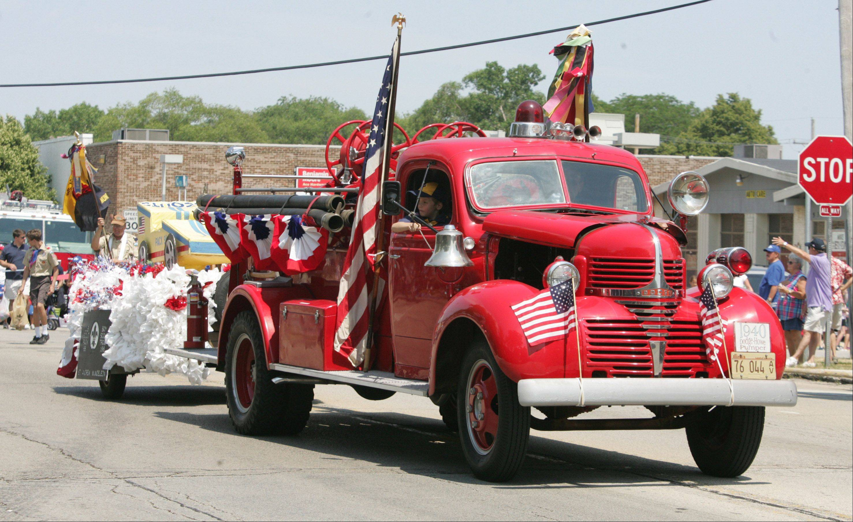 A 1940 Dodge-Howe Pumper fire truck pulls the float for Cub Scouts Pack 98 and Boy Scouts Troop 198 in Mundelein during the Mundelein Community Days Parade Sunday as it makes its way along Hawley Street.