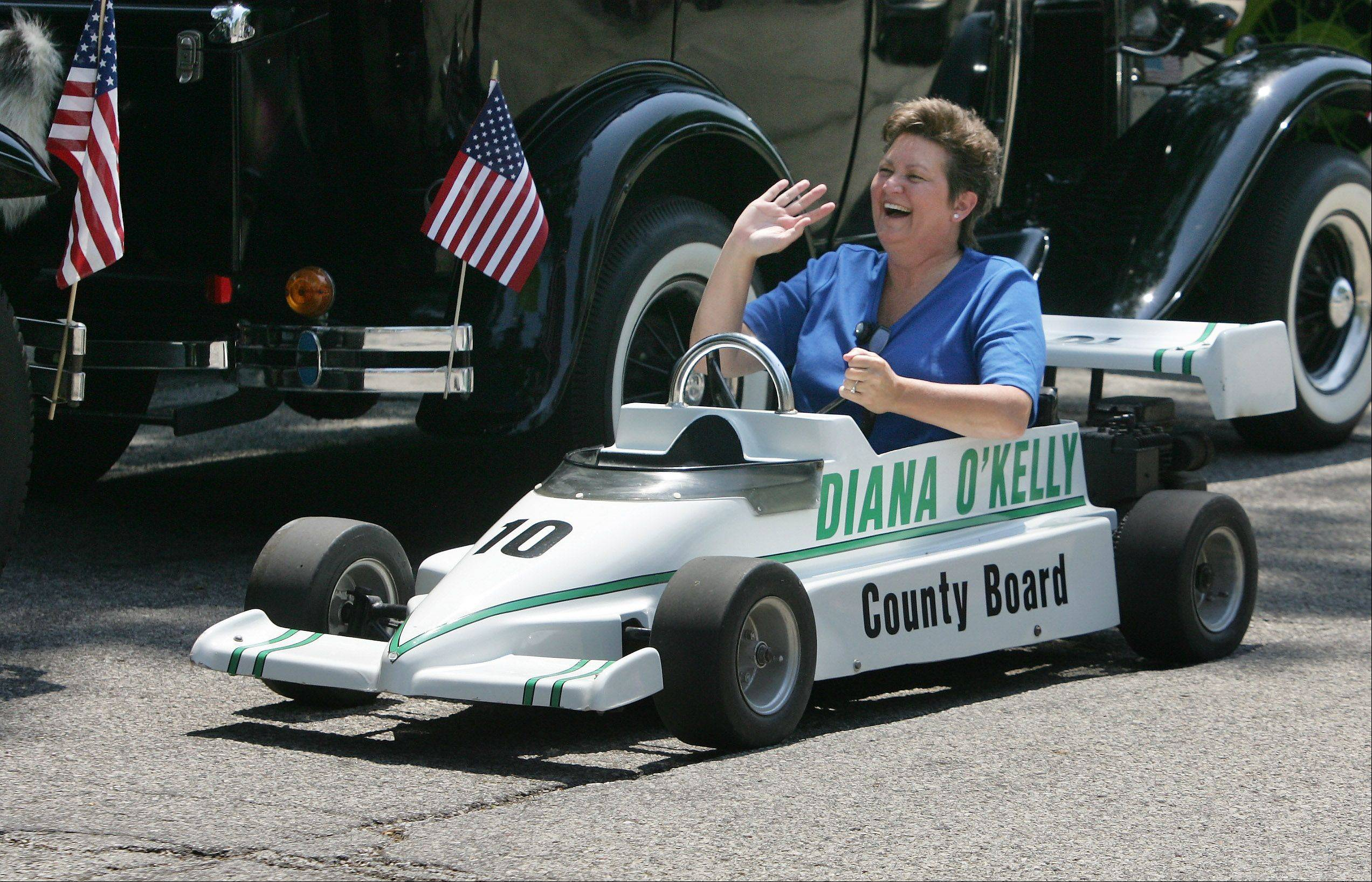Lake County Board member Diana O'Kelly waves as she drives a mini race car during the Mundelein Community Days Parade Sunday as it makes its way along Hawley Street.
