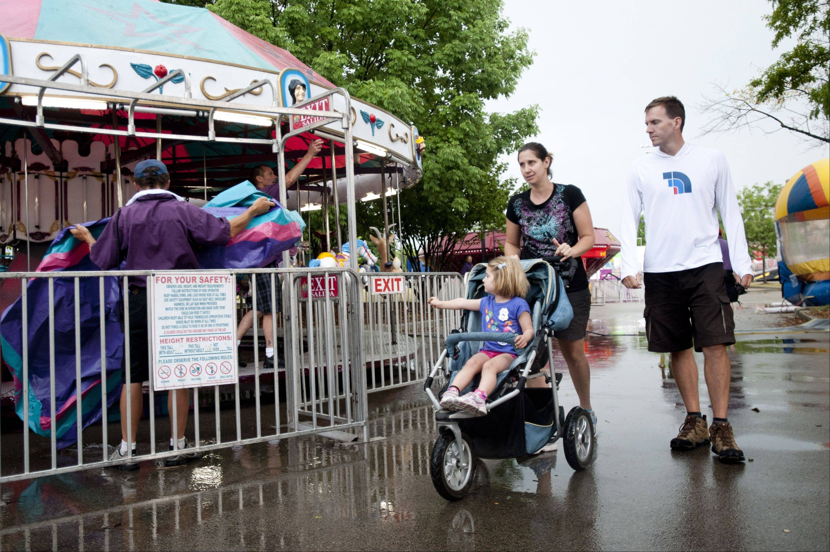 The Snart family strolls through an empty carnival after storms dumped rain on Lisle's Eye to Skies Festival on Sunday.