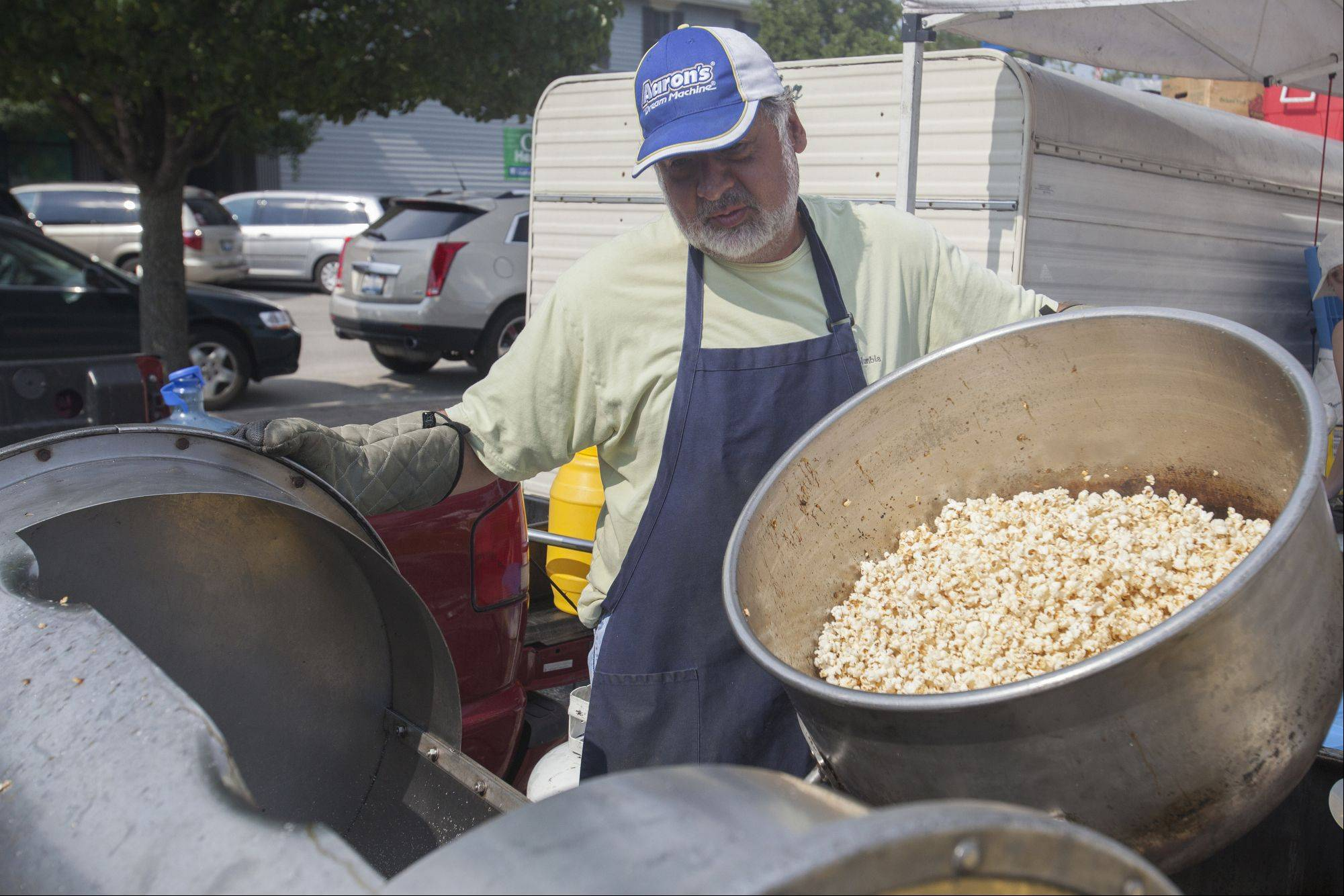 Caros Vidrio pours popcorn into warmer during Mundelein's Farmers Market, located on the corner of Seymour and Park streets.