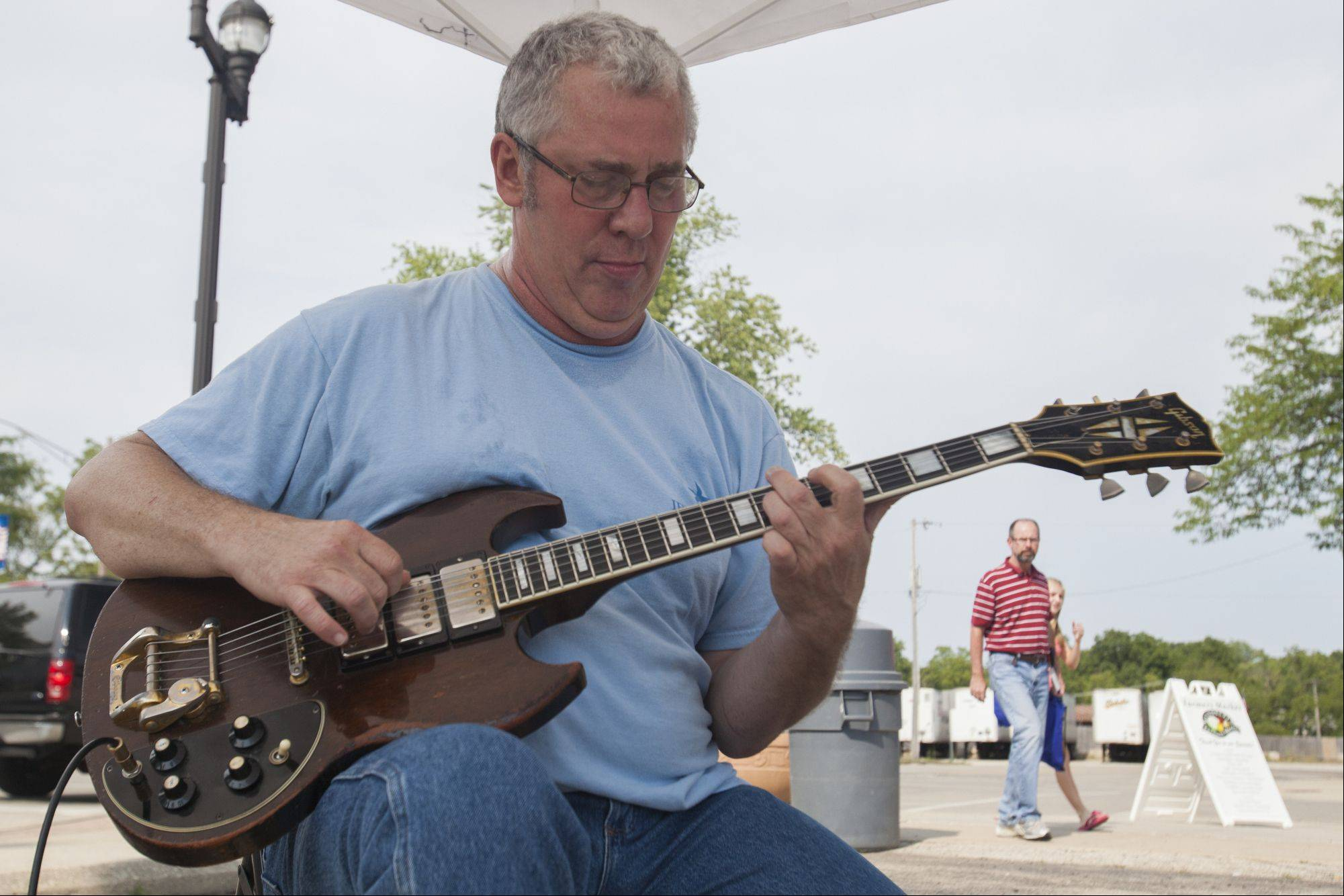 Jazz musician Doug Blake, of Blake N' Blue fame, plays for people as they shop Mundelein's Farmers Market, located at the corner of Seymour and Park Streets.