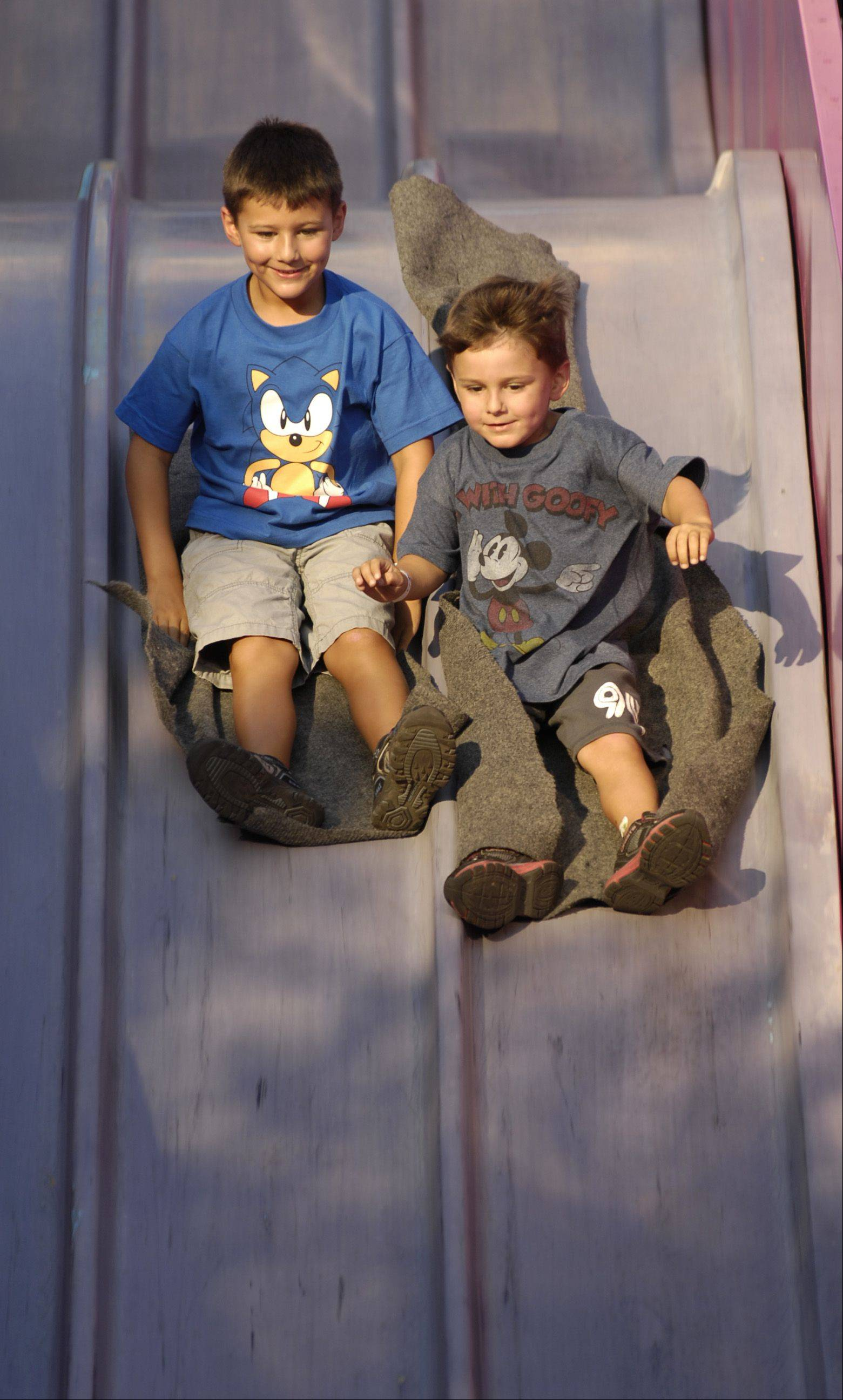 "J.T. and Nate Lang, ages 6 and 4 of Lisle, zoom down the ""Super Slide"" ride at the annual Eyes to the Skies carnival in Lisle."