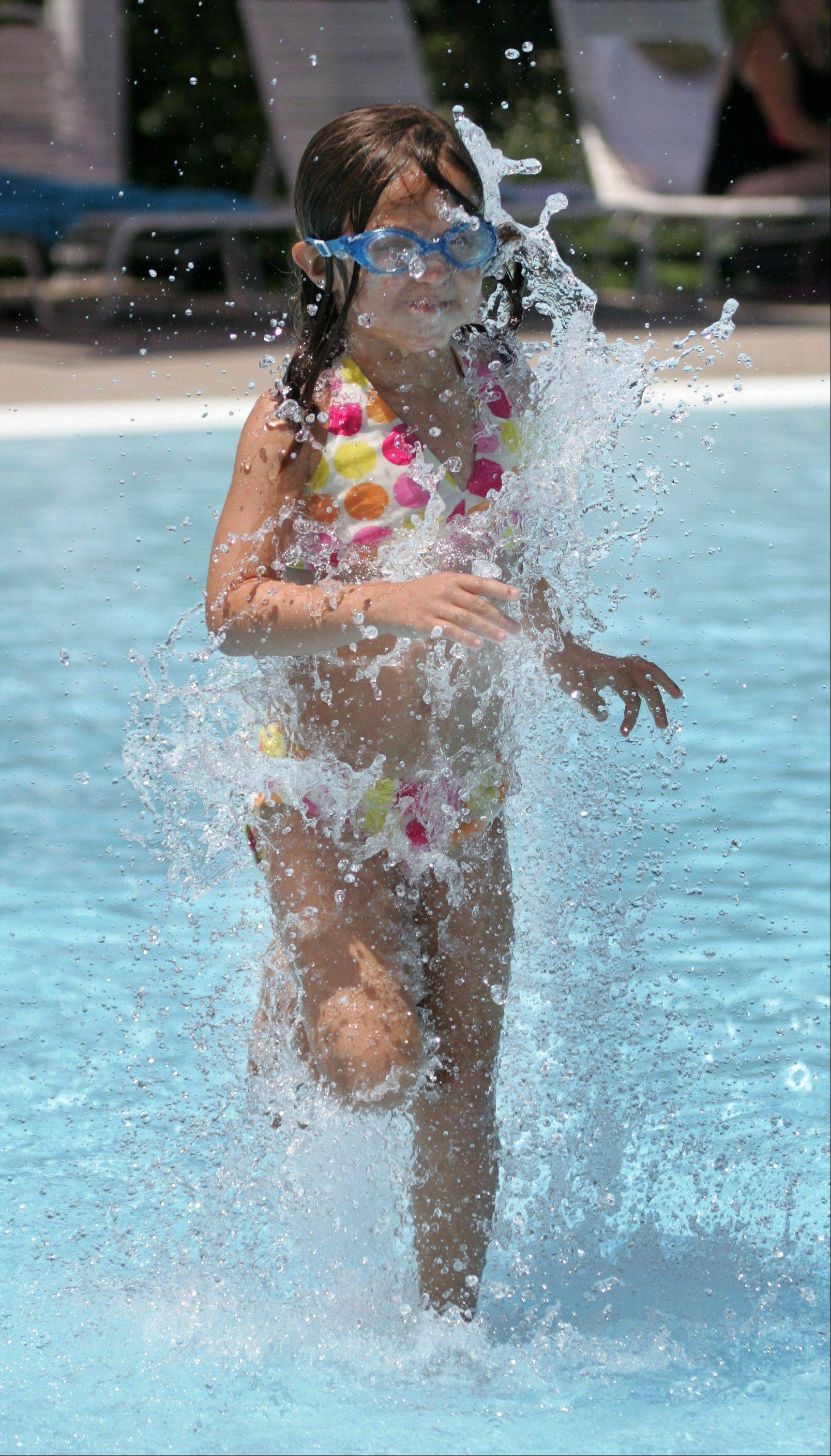 Kylie Poutre, 6, of Mundelein, stands a fountain of water at the Barefoot Bay Family Aquatic Center Wednesday in Mundelein. Residents tried to keep cool as temperatures reached into the 90s.