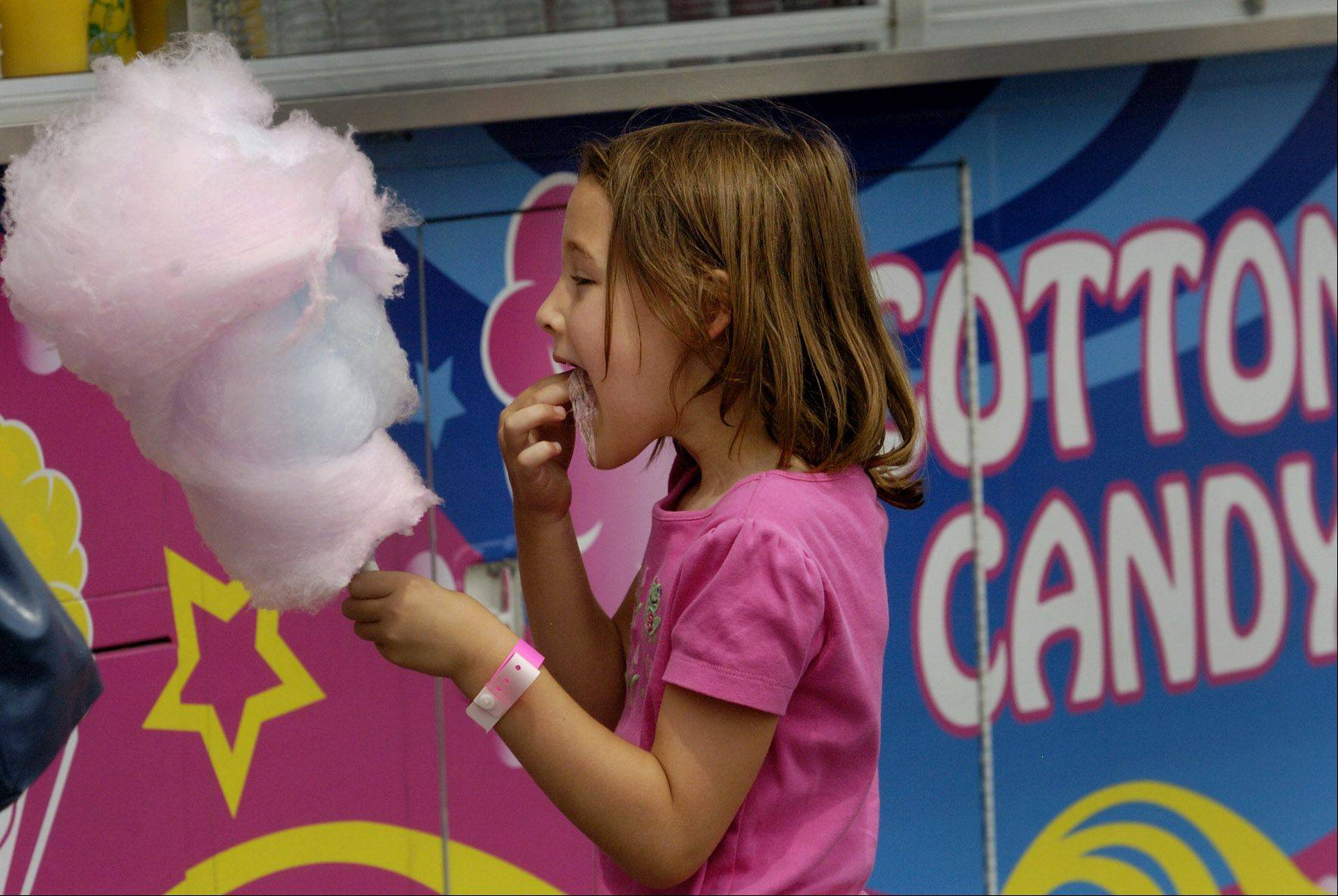 McKenzie Bergefeld of Hawthorn Woods, tries a mouthful of cotton candy at Wauconda Fest in Cook Park.
