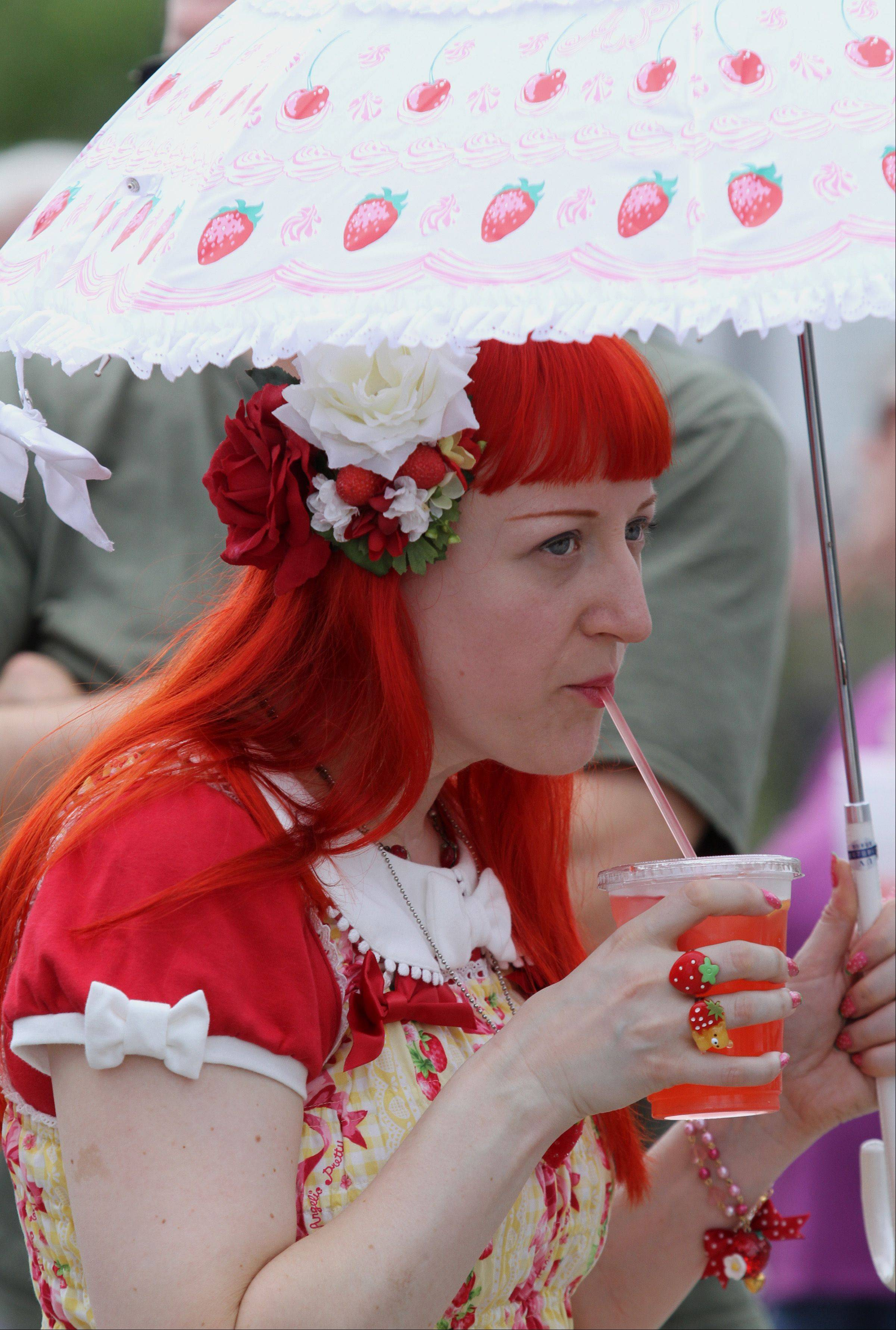 Jola Kupferer of Chicago sips on a strawberry drink at the Long Grove Strawberry Festival on Saturday.
