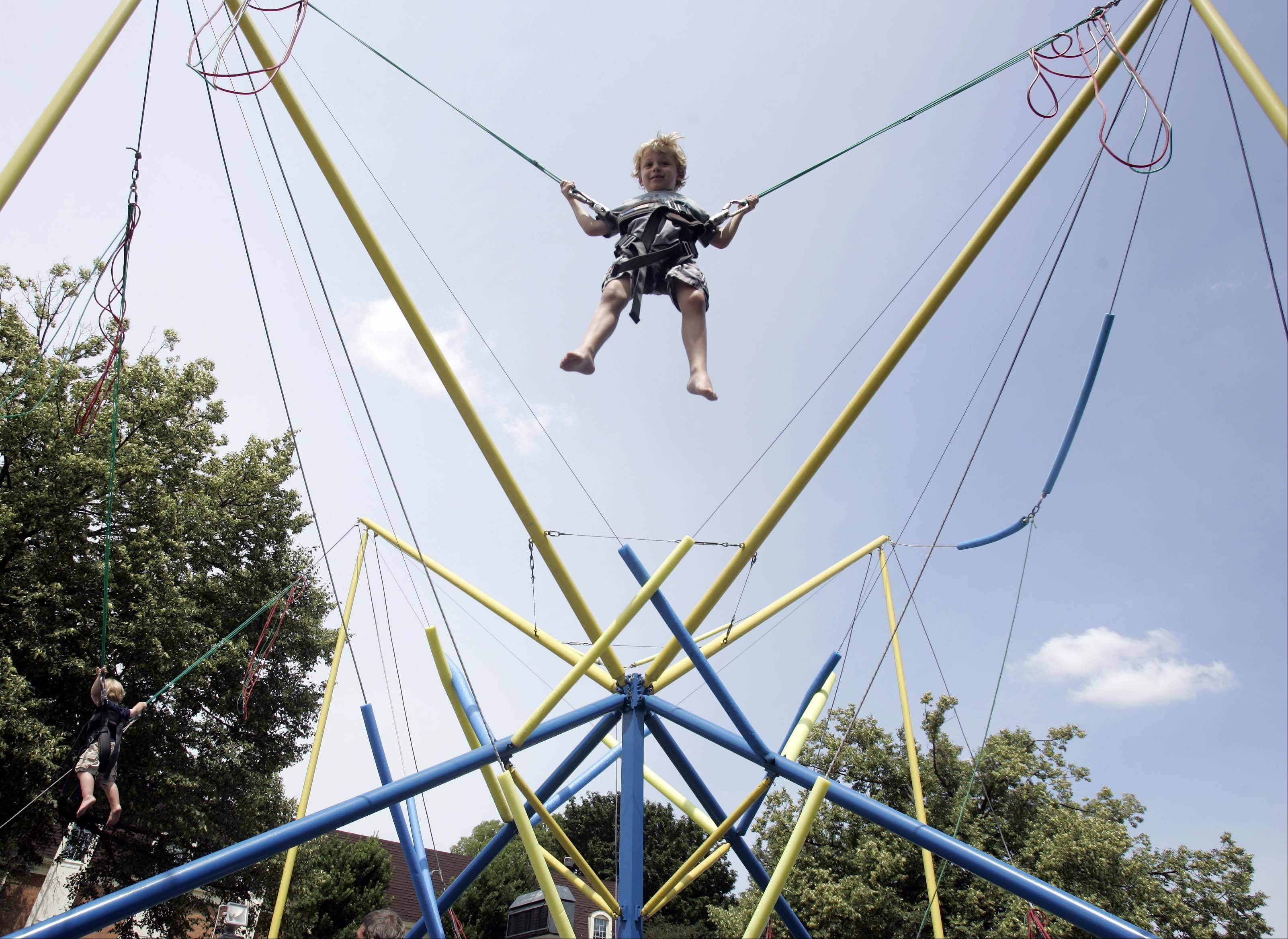 Four-year-old Cole Steben of Geneva gets a birds eye view of Swedish Days in Geneva as he bounces high in the air Saturday June 23, 2012.